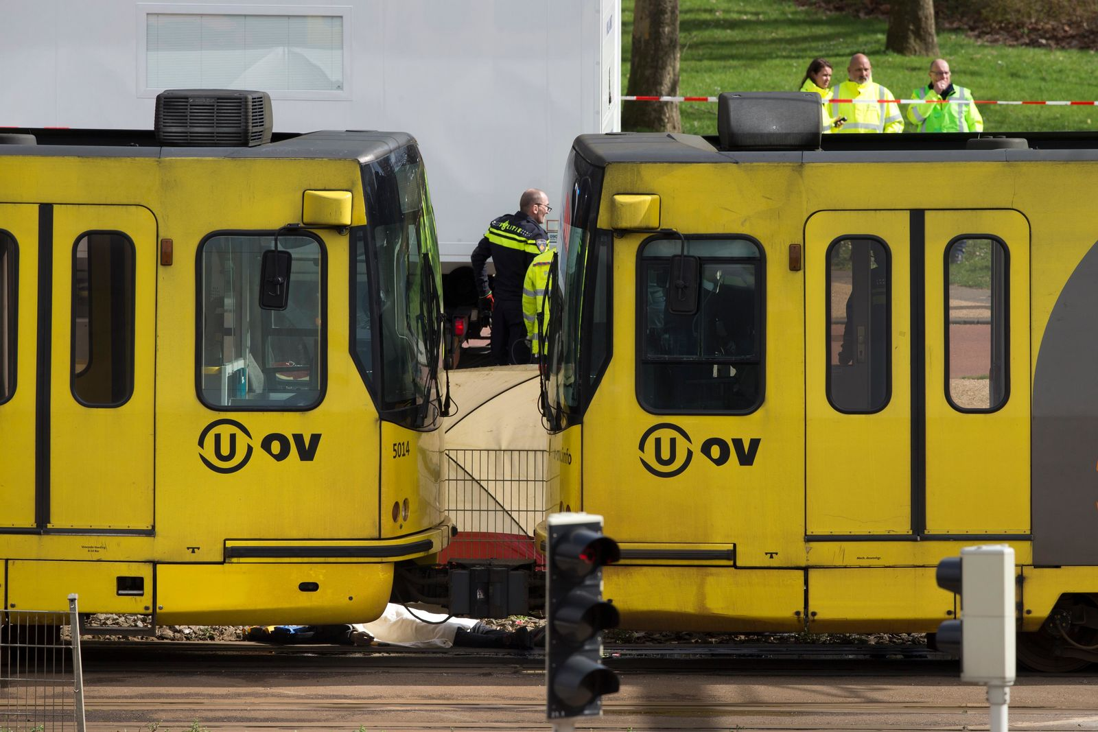 The body of one of three victims is covered with a white sheet as it lies next to a tram after a shooting incident in Utrecht, Netherlands, Monday, March 18, 2019. (AP Photo/Peter Dejong)