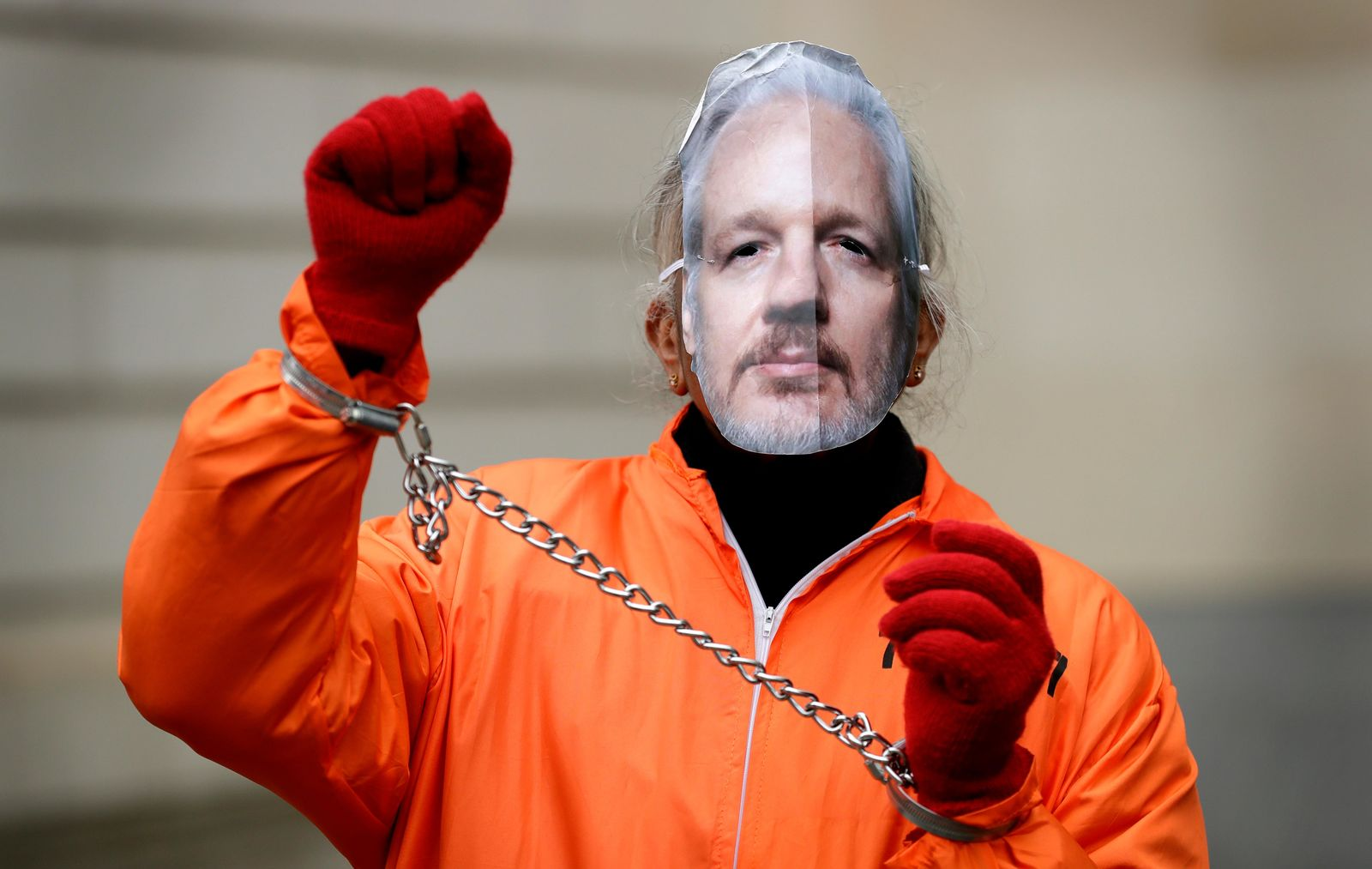 A demonstrator supporting Julian Assange wears a mask and chains outside Westminster Magistrates Court in London, Thursday, Jan. 23, 2020.{ } (AP Photo/Kirsty Wigglesworth)