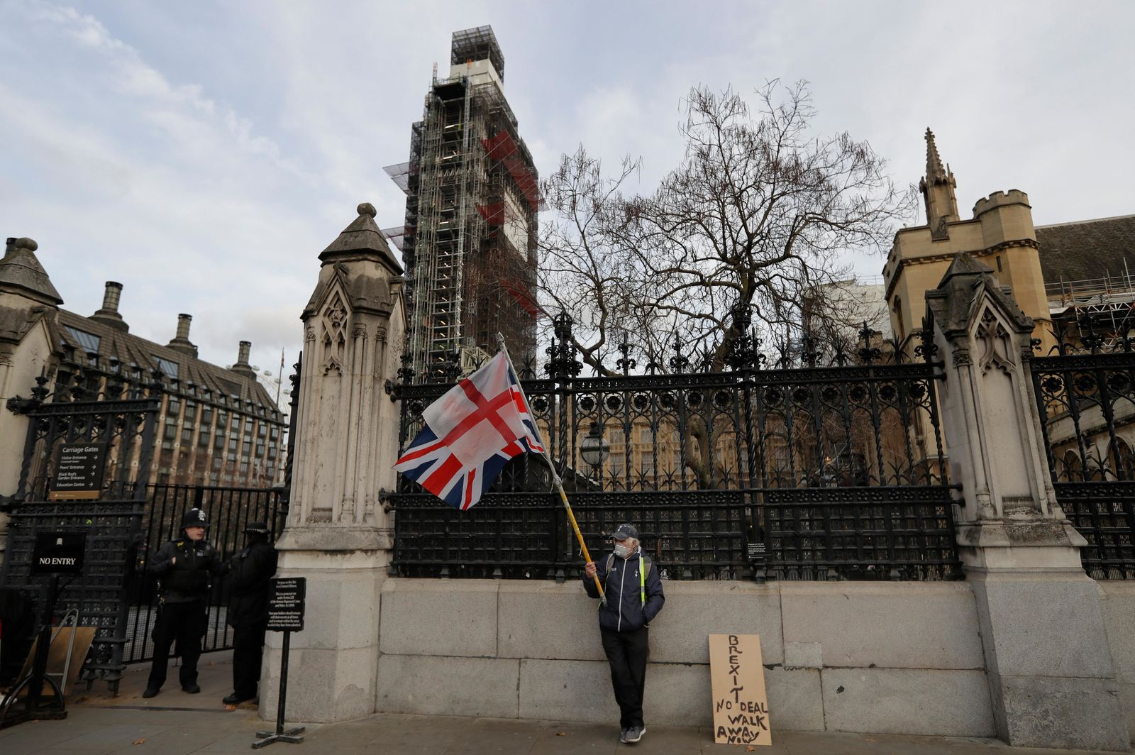 A lone demonstrator stands by an entrance to Britain's parliament in London, Friday, Jan. 18. (AP Photo/Kirsty Wigglesworth)