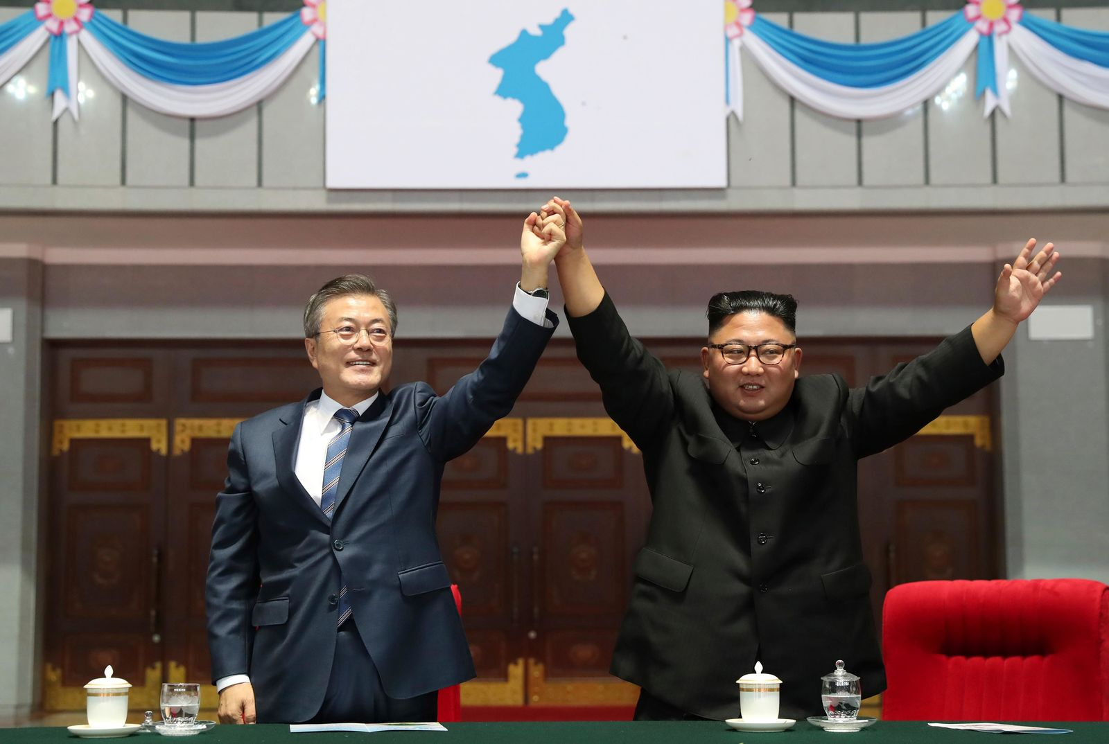 "South Korean President Moon Jae-in and North Korean leader Kim Jong Un raise their hands after watching the mass games performance of ""The Glorious Country"" at May Day Stadium in Pyongyang, North Korea, Wednesday, Sept. 19, 2018. (Pyongyang Press Corps Pool via AP)"