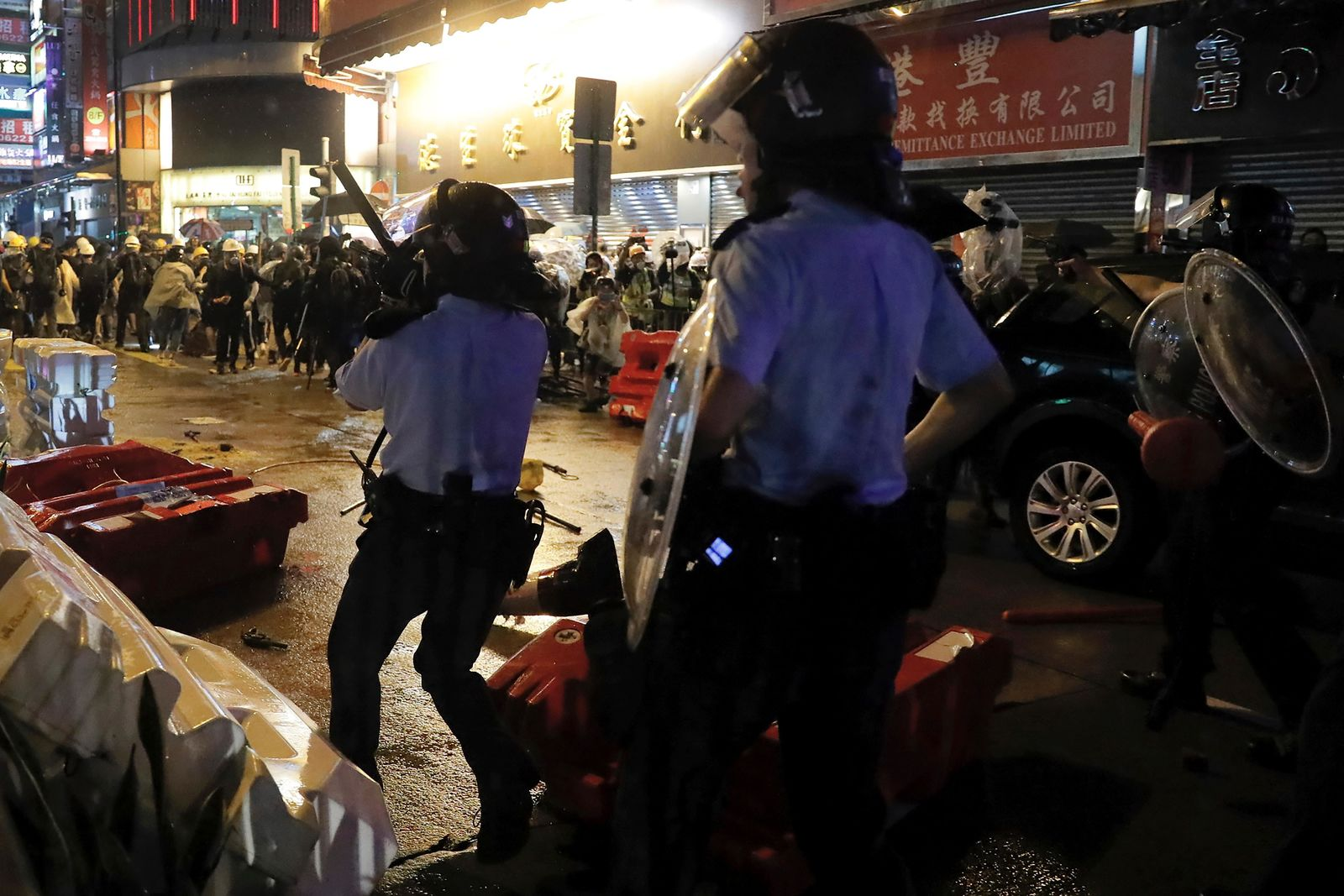 A policeman's gun was dropped on the floor, left, after clashed with demonstrators on a street during a protest in Hong Kong on Sunday, Aug. 25, 2019.{ } (AP Photo/Kin Cheung)