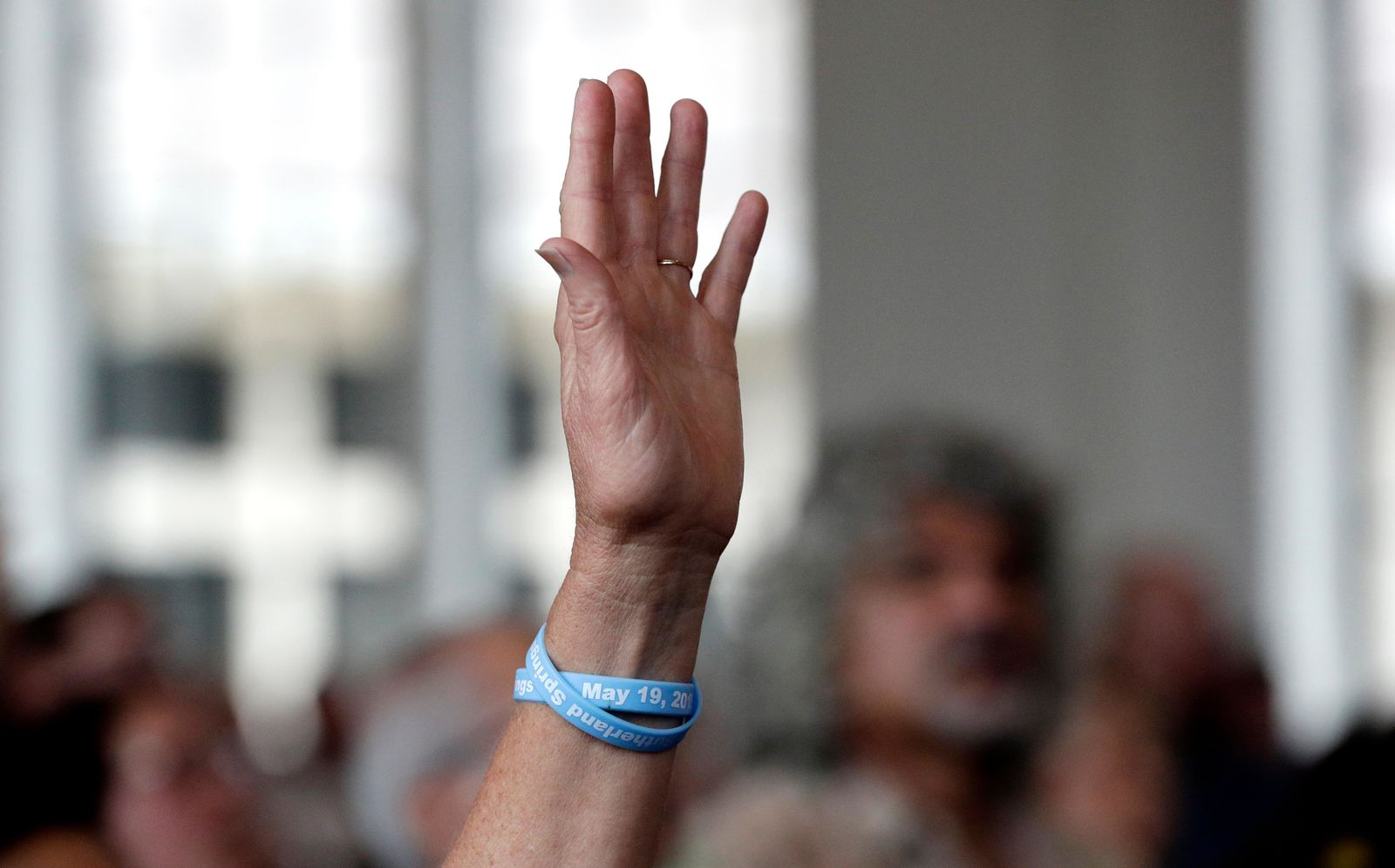 A woman holds her hands in the air a music plays during a dedication ceremony for a new sanctuary and memorial room at the First Baptist Church in Sutherland Springs, Texas, Sunday, May 19, 2019. In 2017 a gunman opened fire at the church and killed more than two dozen congregants. (AP Photo/Eric Gay)
