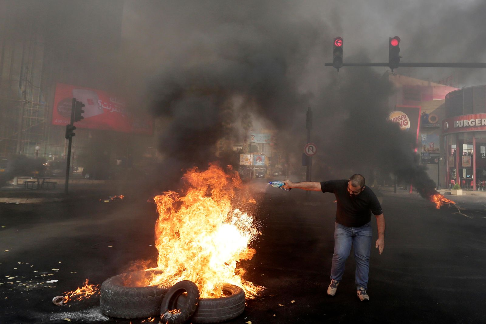 An anti-government protester sets fire on tires to block a road during a protest against government's plans to impose new taxes in Beirut, Lebanon, Friday, Oct. 18, 2019. (AP Photo/Hassan Ammar)