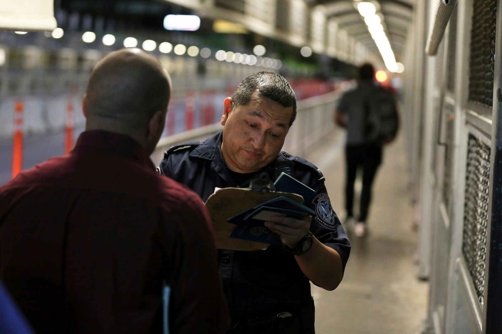 A U.S. Customs and Border Protection officer checks the documents of migrants who are on their way to apply for asylum in the United States, on International Bridge 1 as they depart Nuevo Laredo, Mexico, early Tuesday, Sept. 17, 2019.{ } (AP Photo/Fernando Llano)