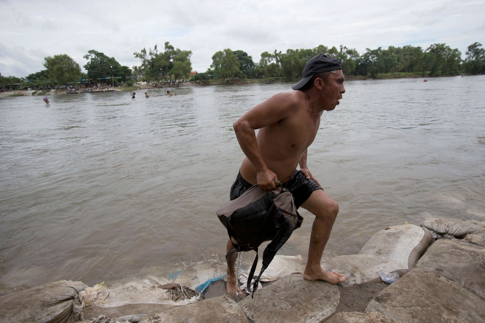 A Central American migrant walks off the shore on the Mexican side of the Suchiate River after wading across, on the the border between Guatemala and Mexico, in Ciudad Hidalgo, Mexico, Saturday, Oct. 20, 2018. (AP Photo/Moises Castillo)