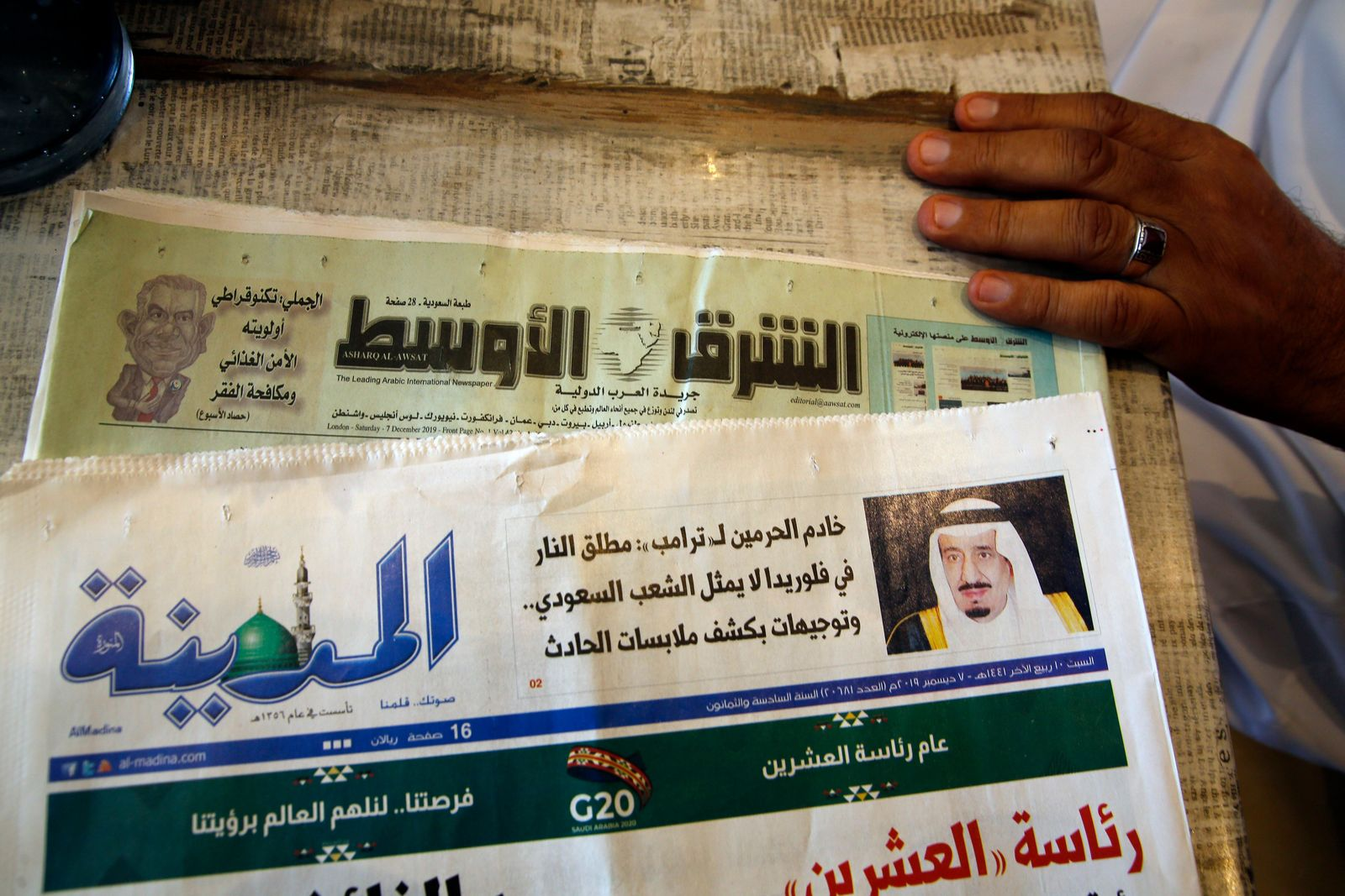 "Saudi daily Al-Madina newspaper fronted by a picture of Saudi King Salman is displayed at a coffee shop in Jiddah, Saudi Arabia, Saturday, Dec. 7, 2019. U.S. law enforcement officials were digging into the background of the suspected Florida naval station shooter Friday, to determine the Saudi Air Force officer's motive and whether it was connected to terrorism. Arabic reads ""King Salman to Donald J"