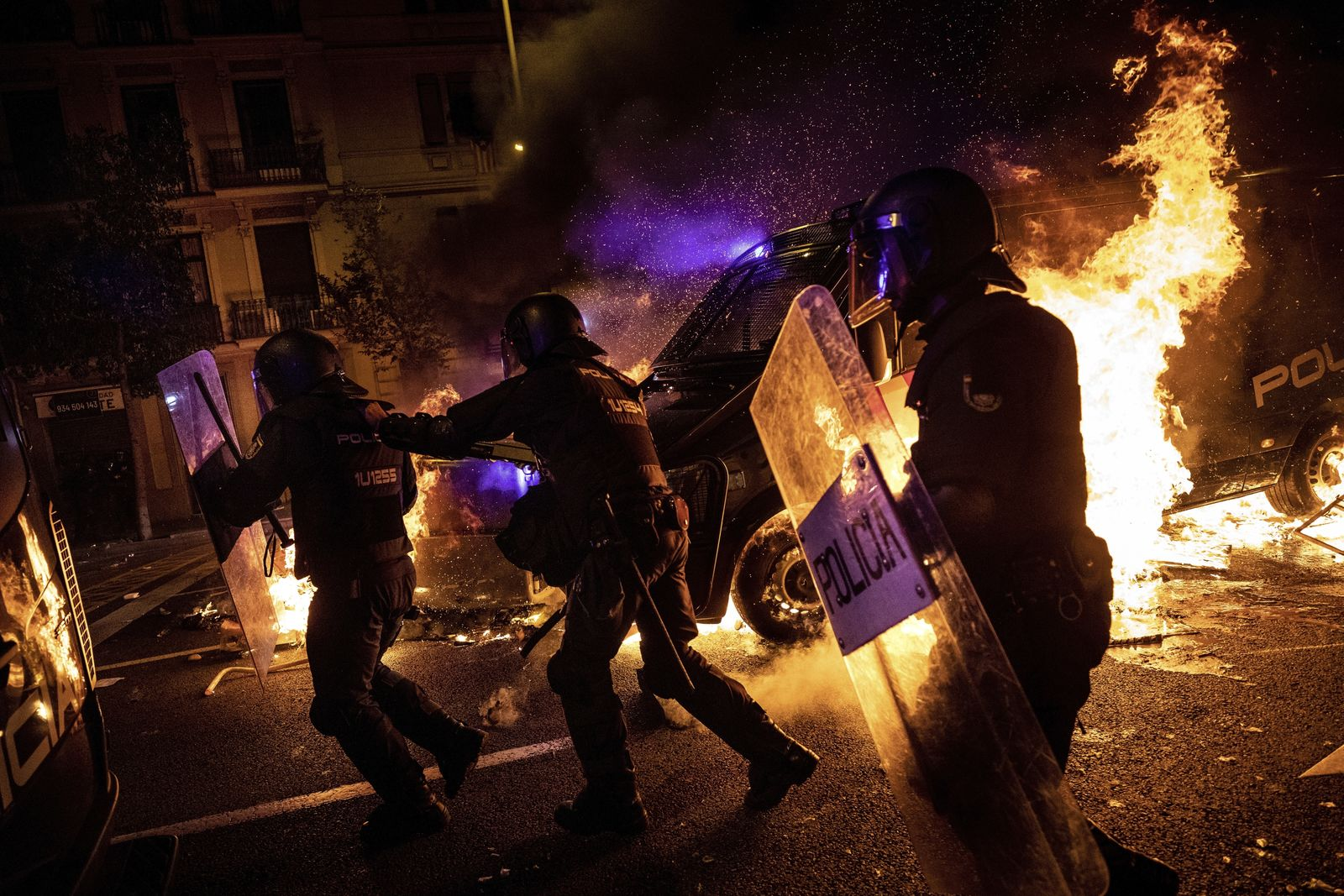 Policemen run as a police van drives over a burning barricade during clashes between protestors and police in Barcelona, Spain, Wednesday, Oct. 16, 2019.{ } (AP Photo/Bernat Armangue)