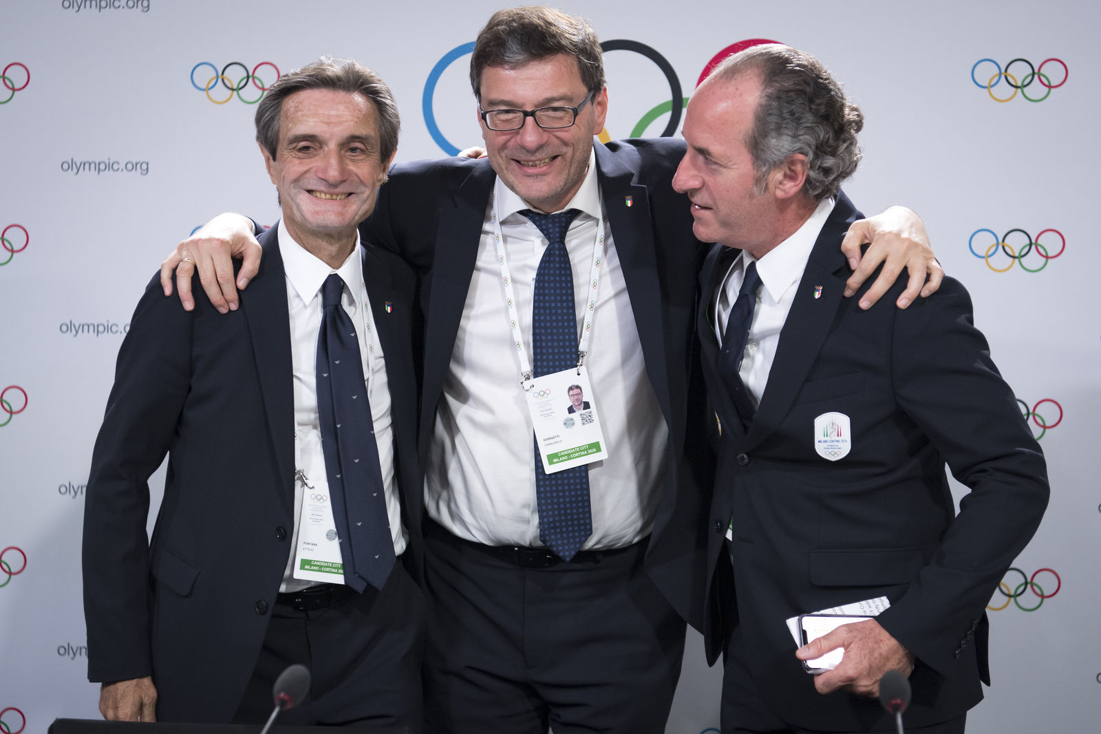 From left, Italy's Lombardy region President Attilio Fontana, Italy's Under Secretary of State Giancarlo Giorgetti and Italy's Veneto Region President Luca Zaia pose after Milan-Cortina won the bid to host the 2026 Winter Olympic Games, during the first day of the 134th Session of the International Olympic Committee (IOC), at the SwissTech Convention Centre, in Lausanne, Switzerland, Monday, June 24, 2019.(Laurent Gillieron/Keystone via AP)