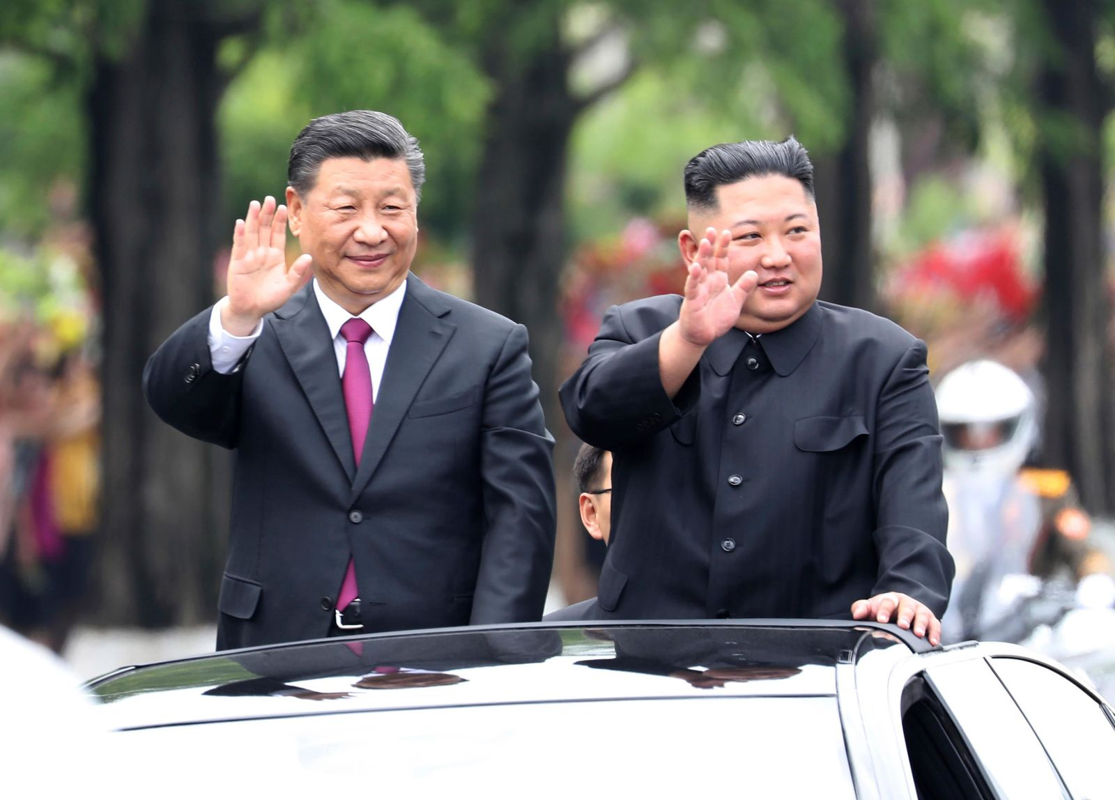 In this Thursday, June 20, 2019, photo released by China's Xinhua News Agency, visiting Chinese President Xi Jinping, left, and North Korean leader Kim Jong Un wave from an open top limousine as they travel along a street in Pyongyang, North Korea. North Korean leader Kim Jong Un, meeting in Pyongyang with Chinese President Xi Jinping, said Thursday that his country is waiting for a desired response in stalled nuclear talks with the United States. (Ju Peng/Xinhua via AP)