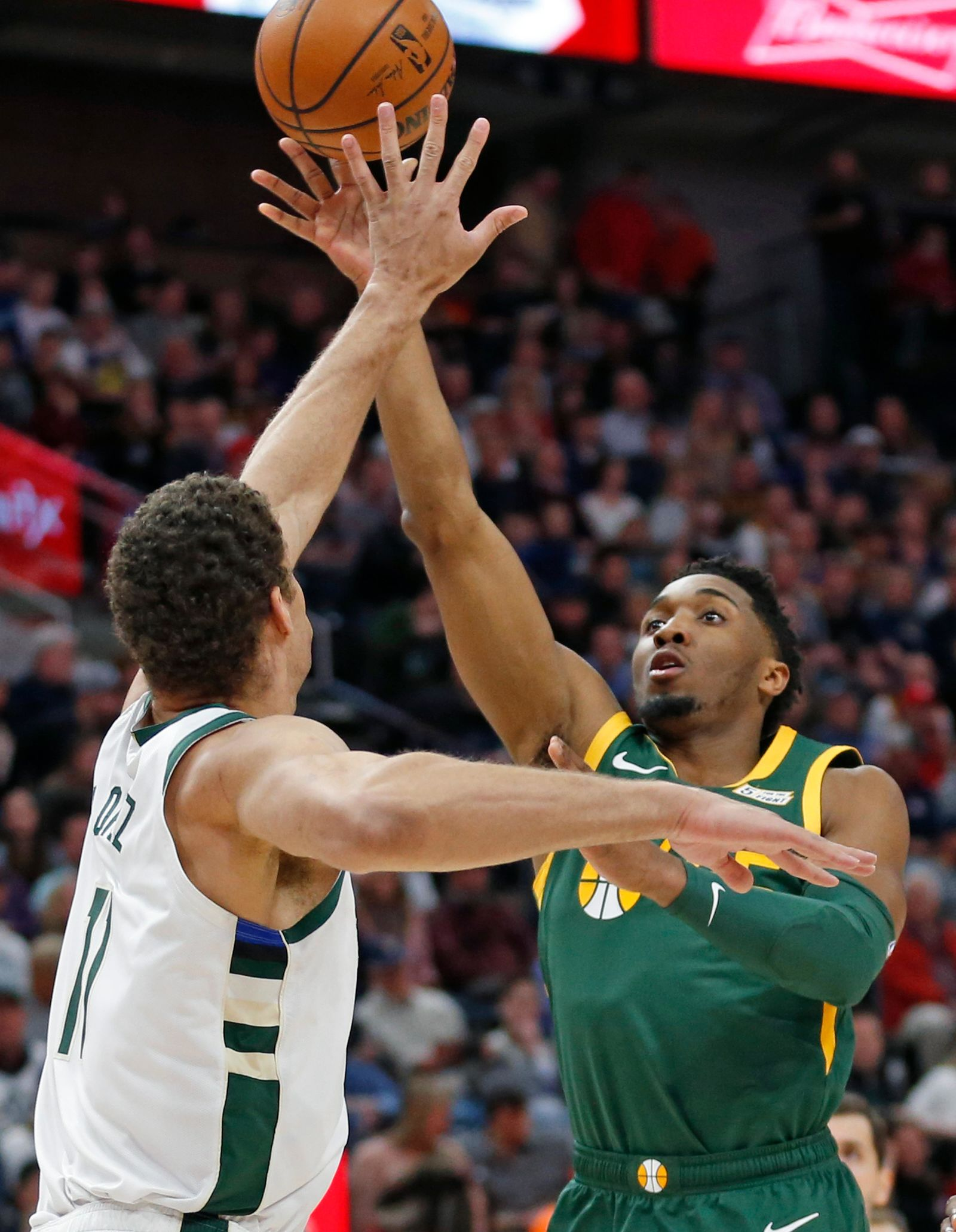 Utah Jazz guard Donovan Mitchell, right, lays the ball up as Milwaukee Bucks center Brook Lopez, left, defends during the first half of an NBA basketball game Saturday, March 2, 2019, in Salt Lake City. (AP Photo/Rick Bowmer)