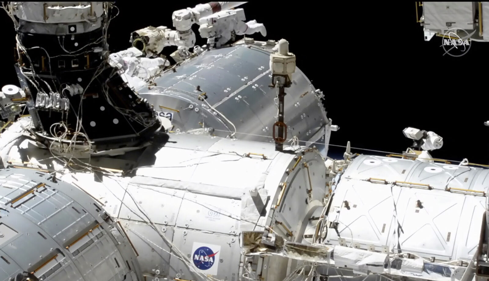 In this image taken from NASA video, NASA astronauts Mike Hopkins, center right, and Victor Glover, center left, work outside the International Space Station's European lab on Wednesday, Jan. 27, 2021. (NASA via AP)