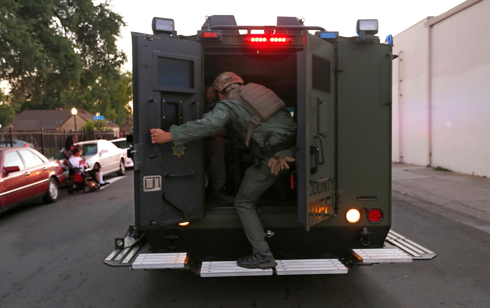 A law enforcement officer climbs into a tactical vehicle during a standoff with an armed suspect who has taken refuge after shooting a Sacramento police officer, Wednesday, June 19, 2019, in Sacramento, Calif. (AP Photo/Rich Pedroncelli)