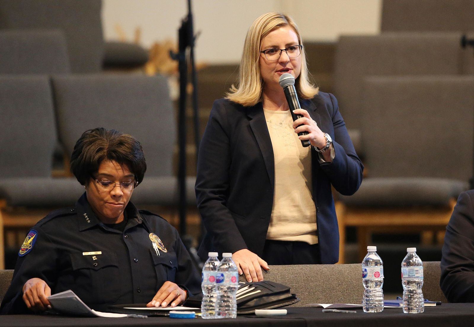 Phoenix Mayor Kate Gallego, right, addresses the audience as Phoenix Police Chief Jeri Williams, left, goes through notes at a community meeti