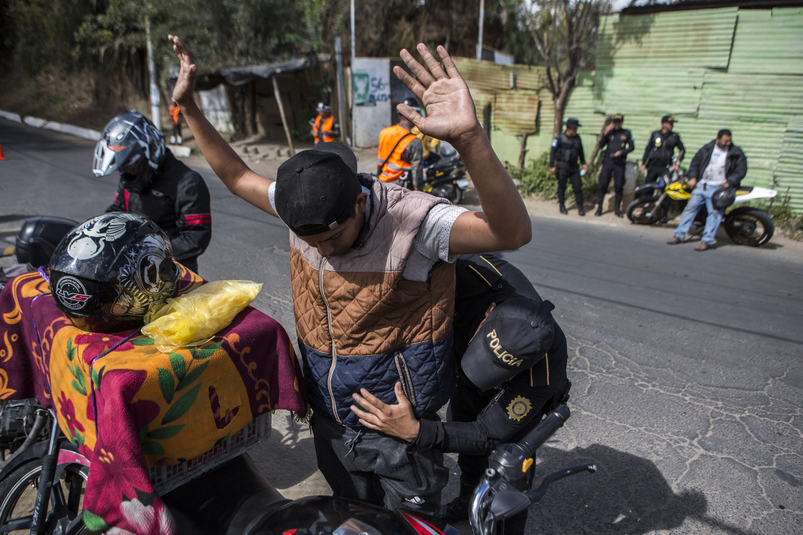 A police stops a motorcyclist to search him at a security checkpoint in the El Milagro area of the Mixco municipality on the outskirts of Guatemala City, Friday, Jan. 17, 2020.{ } (AP Photo/Oliver de Ros)