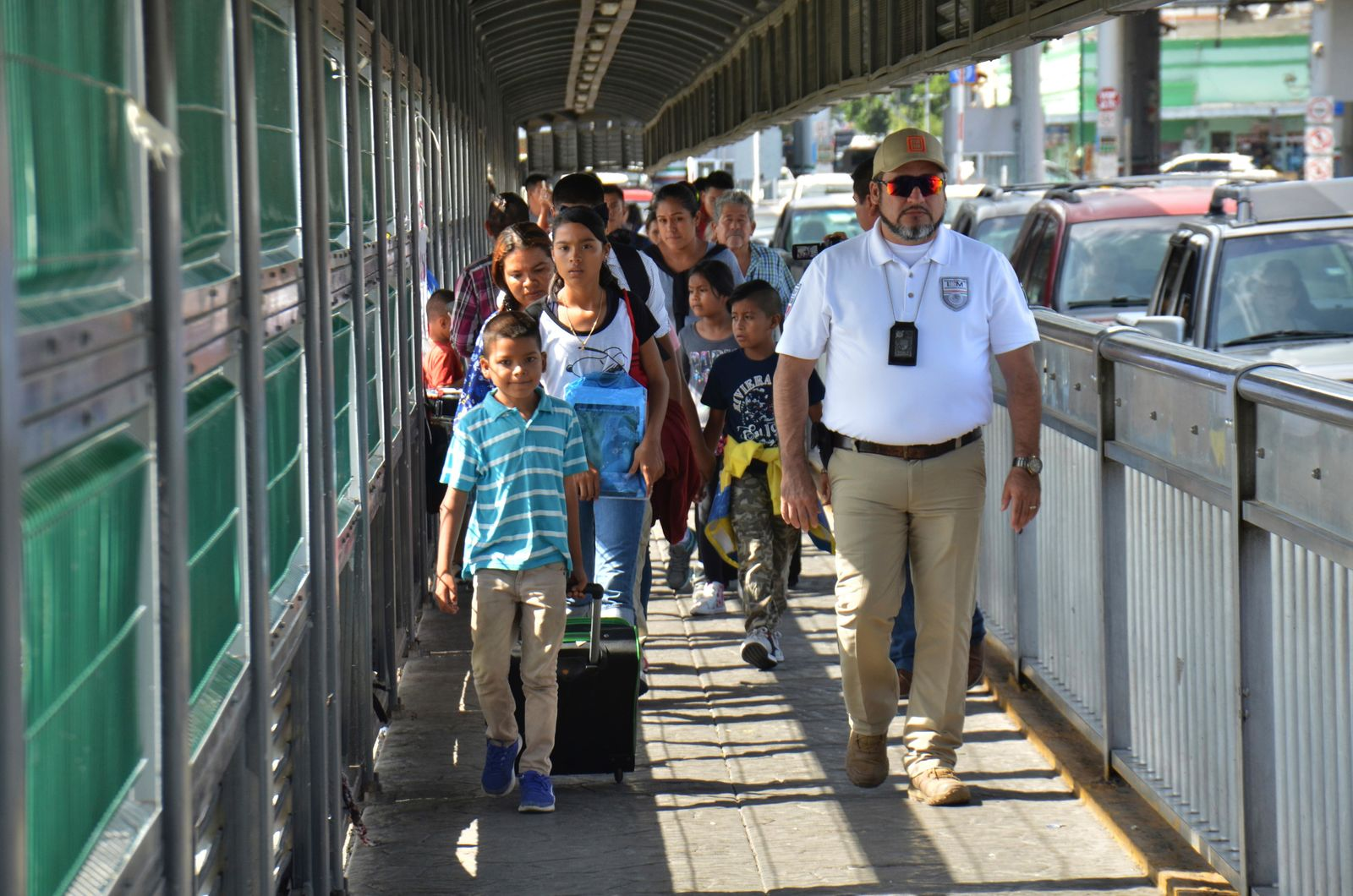 A Mexican migration officer escorts a group of migrants to apply for asylum in the United States, on the International Bridge 1 in Nuevo Laredo, Mexico. (AP Photo/Salvador Gonzalez)