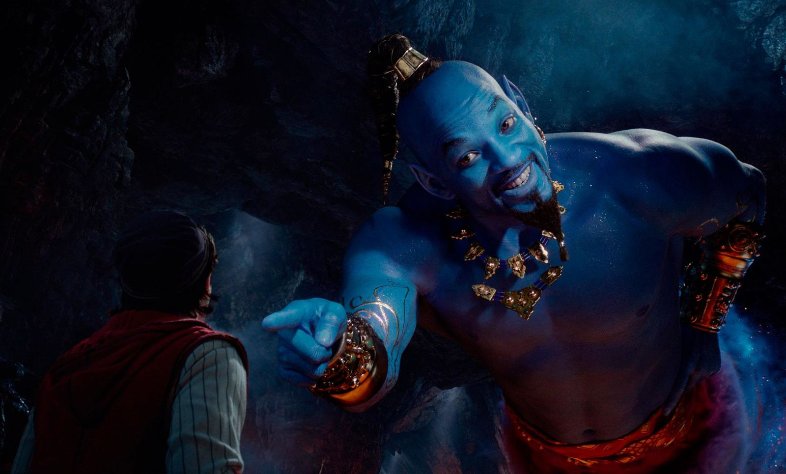"This image released by Disney shows Mena Massoud as Aladdin, left, and Will Smith as Genie in Disney's live-action adaptation of the 1992 animated classic ""Aladdin.""  (Disney via AP)"