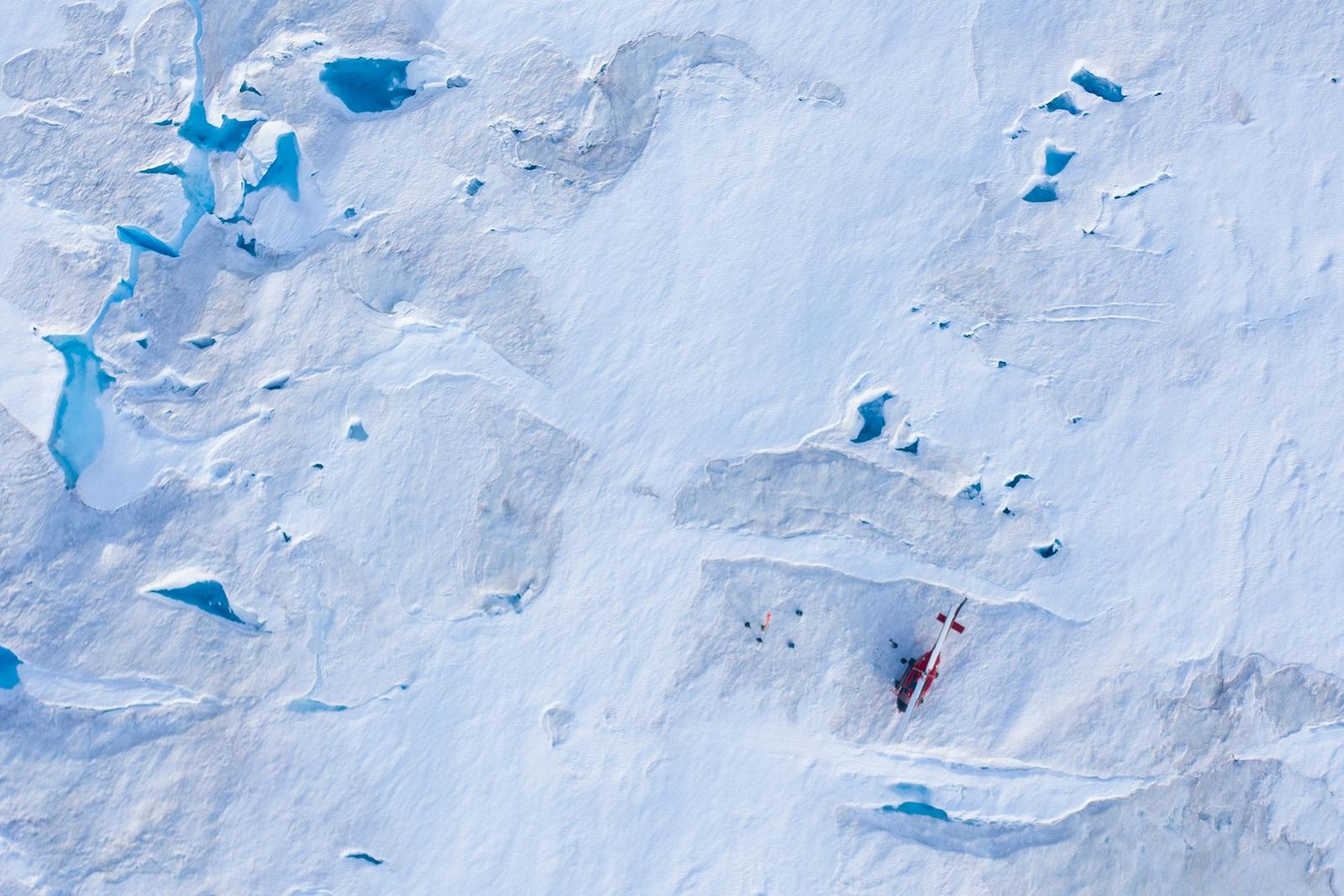 In this Aug. 16, 2019, photo, a helicopter carrying New York University air and ocean scientist David Holland and his team sits on the ice as they install a radar and GPS at the Helheim glacier, in Greenland.{ } (AP Photo/Felipe Dana)