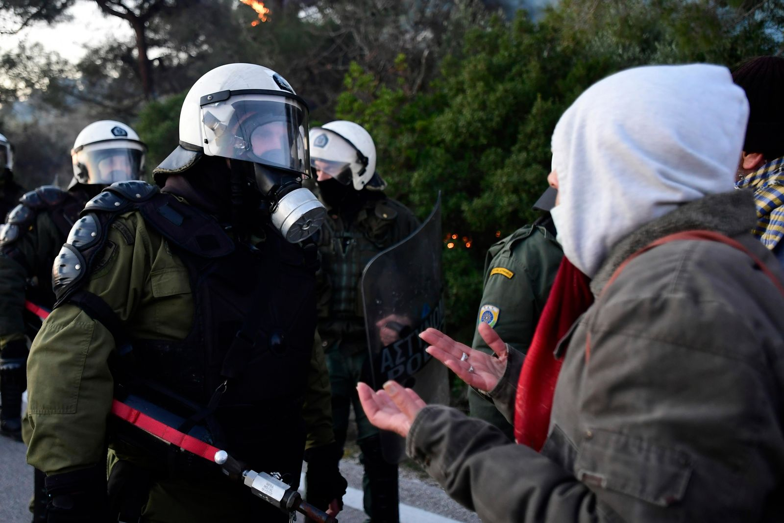 A protester reacts as riot police block a road in Karava village near the area where the government plans to build a new migrant detention center, on the northeastern Aegean island of Lesbos, Greece, early Tuesday, Feb. 25, 2020.{ } (AP Photo/Michael Varaklas)
