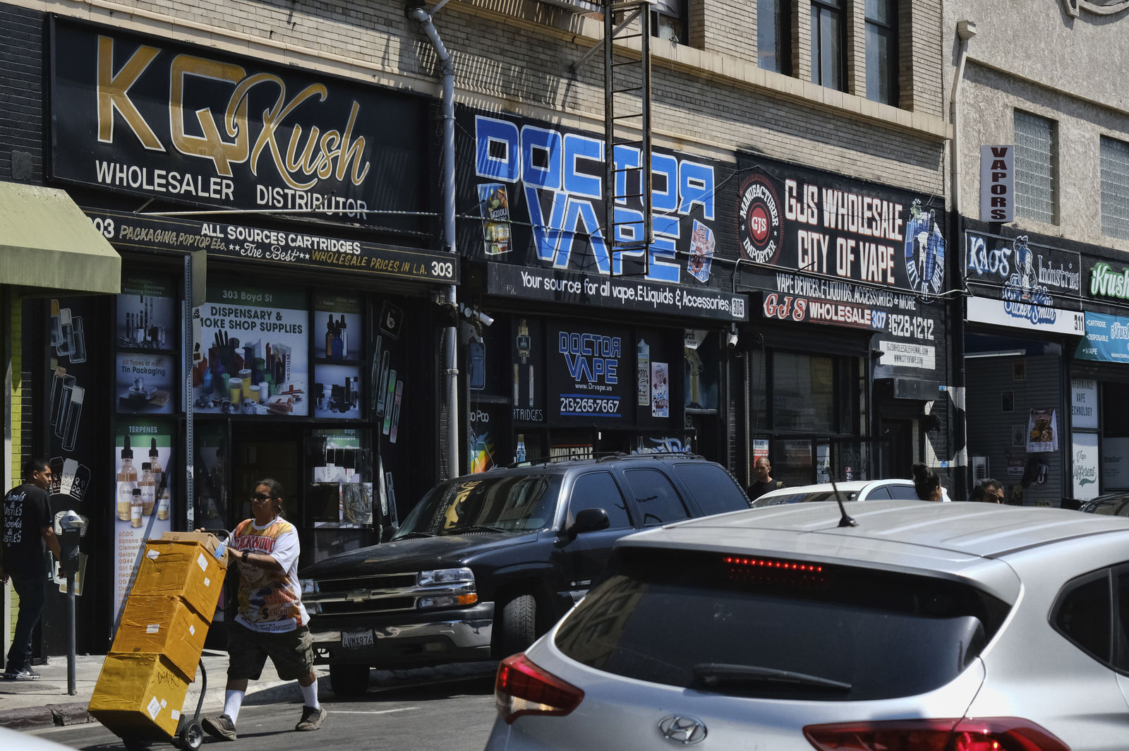 FILE - This Aug. 28, 2019, file photo shows a bustling street lined with wholesale vape shops in downtown Los Angeles. AP Photo/Richard Vogel, File)