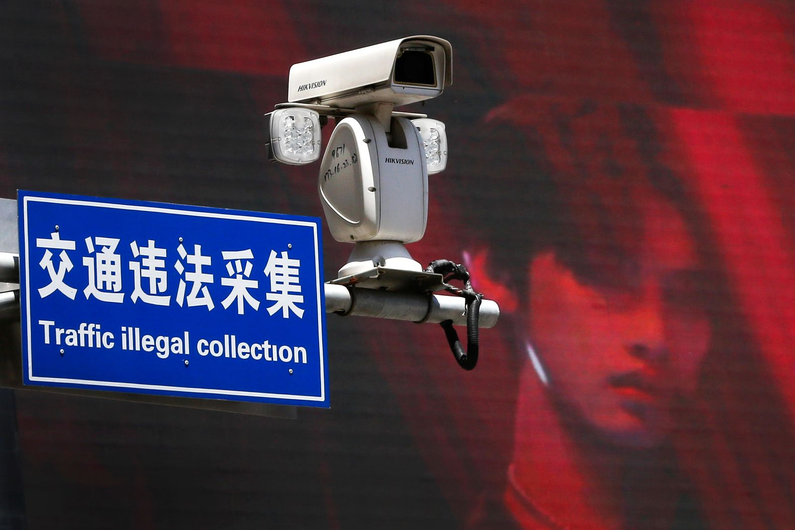 A surveillance camera made by China's Hikvision is mounted on top of a street against a huge TV screen in Beijing, Thursday, May 23, 2019. The Chinese video surveillance company says it is taking concern about the use of its technology seriously following a report that the U.S. may block several Chinese surveillance companies from buying American components. (AP Photo/Andy Wong)