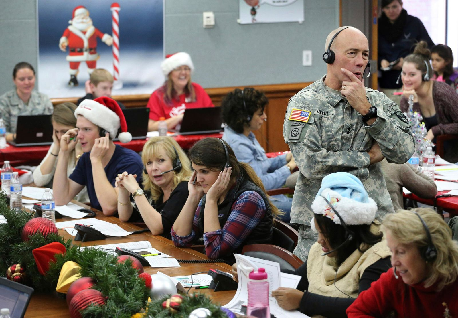 FILE - In this Dec. 24, 2014, file photo, NORAD Chief of Staff Maj. Gen. Charles D. Luckey takes a call while volunteering at the NORAD Tracks Santa center at Peterson Air Force Base in Colorado Springs, Colo. Hundreds of volunteers will help answer the phones from children around the world calling for Santa when the program resumes on Monday, Dec. 24, 2018, for the 63rd year. (AP Photo/Brennan Linsley, File)
