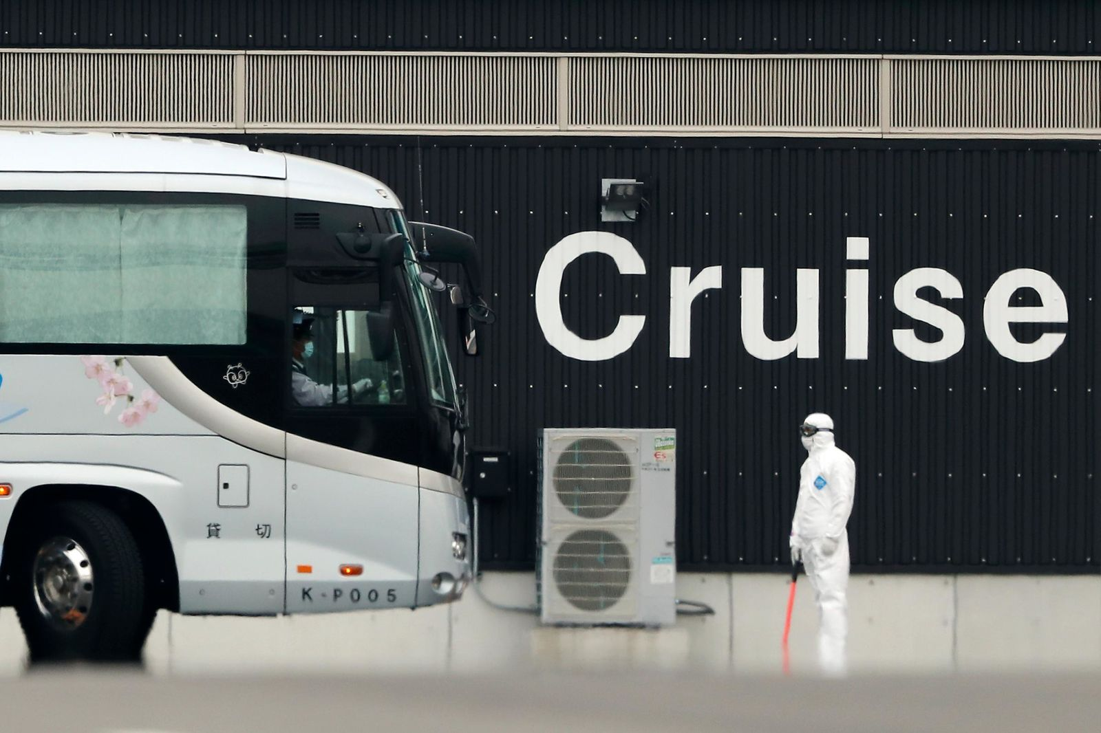 A bus carrying the passengers from the quarantined Diamond Princess cruise ship prepares to leave a port in Yokohama, near Tokyo, Thursday, Feb. 20, 2020.{ } (AP Photo/Eugene Hoshiko)