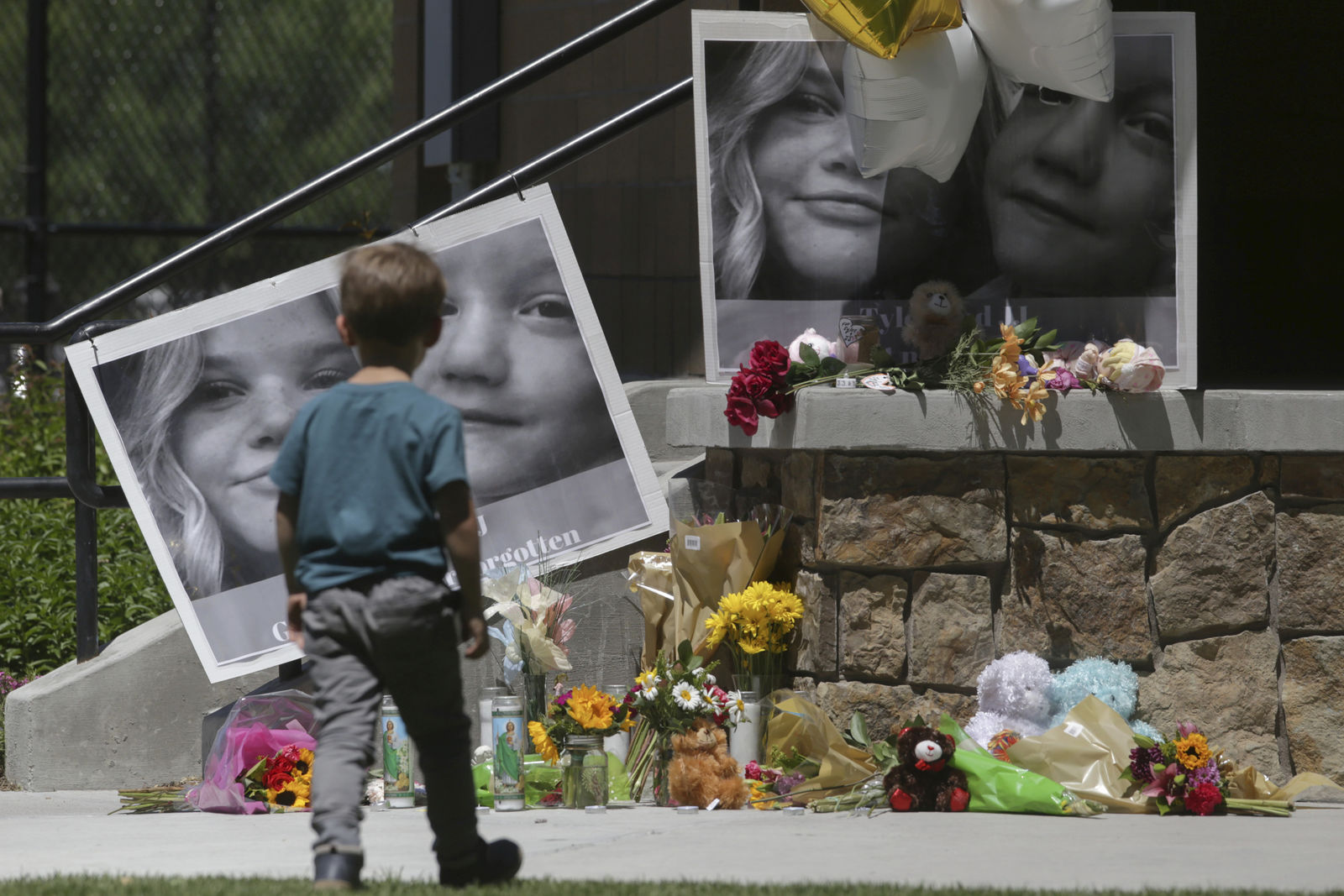 "FILE - In this June 11, 2020, file photo, a boy looks at a memorial for Tylee Ryan, 17, and Joshua ""JJ"" Vallow, 7, at Porter Park in Rexburg, Idaho. An Idaho prosecutor is expected Monday, Aug. 3, 2020, to begin sketching out his case against an Idaho couple at the center of a bizarre missing children's case that ended in tragedy when their bodies were found buried on a rural eastern Idaho property earlier this year. (John Roark/The Idaho Post-Register via AP, File)"