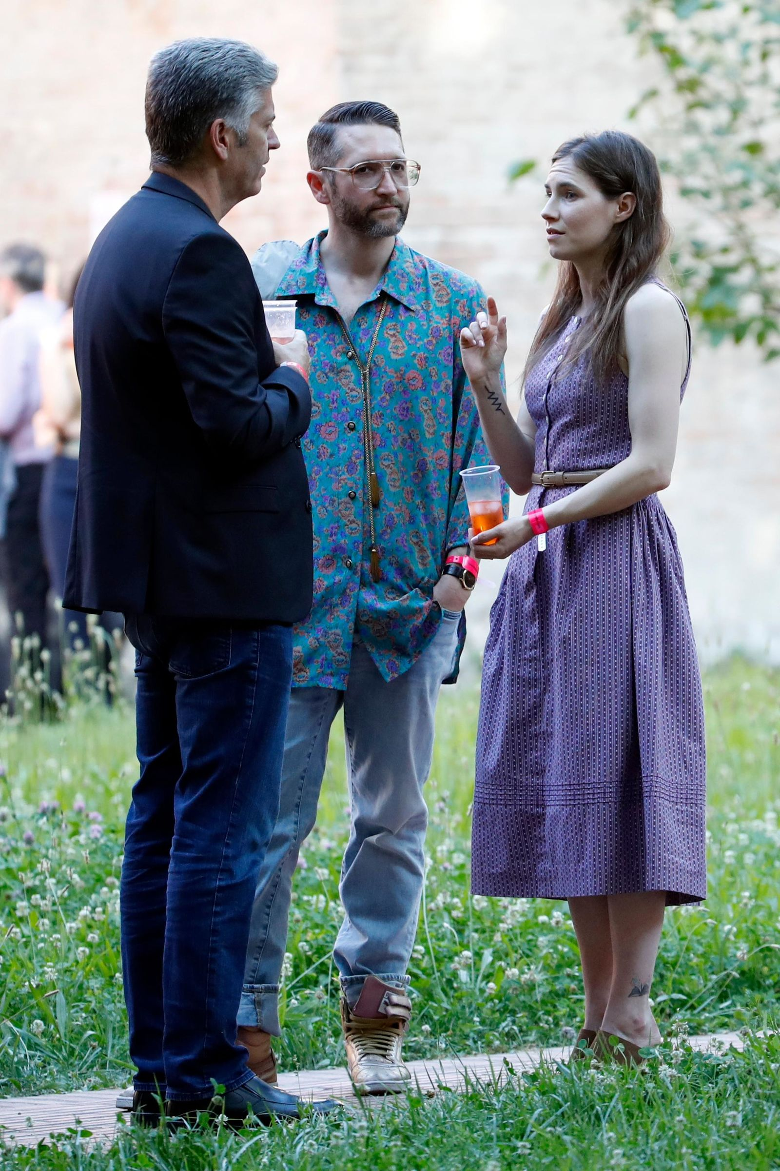 Amanda Knox, right, and her boyfriend Christopher Robinson, center, talk with a guest as they attend a cocktail for the opening of the Innocence Project conference, in Modena, Italy, Thursday, June 13, 2019.(AP Photo/Antonio Calanni)(AP Photo/Antonio calanni)
