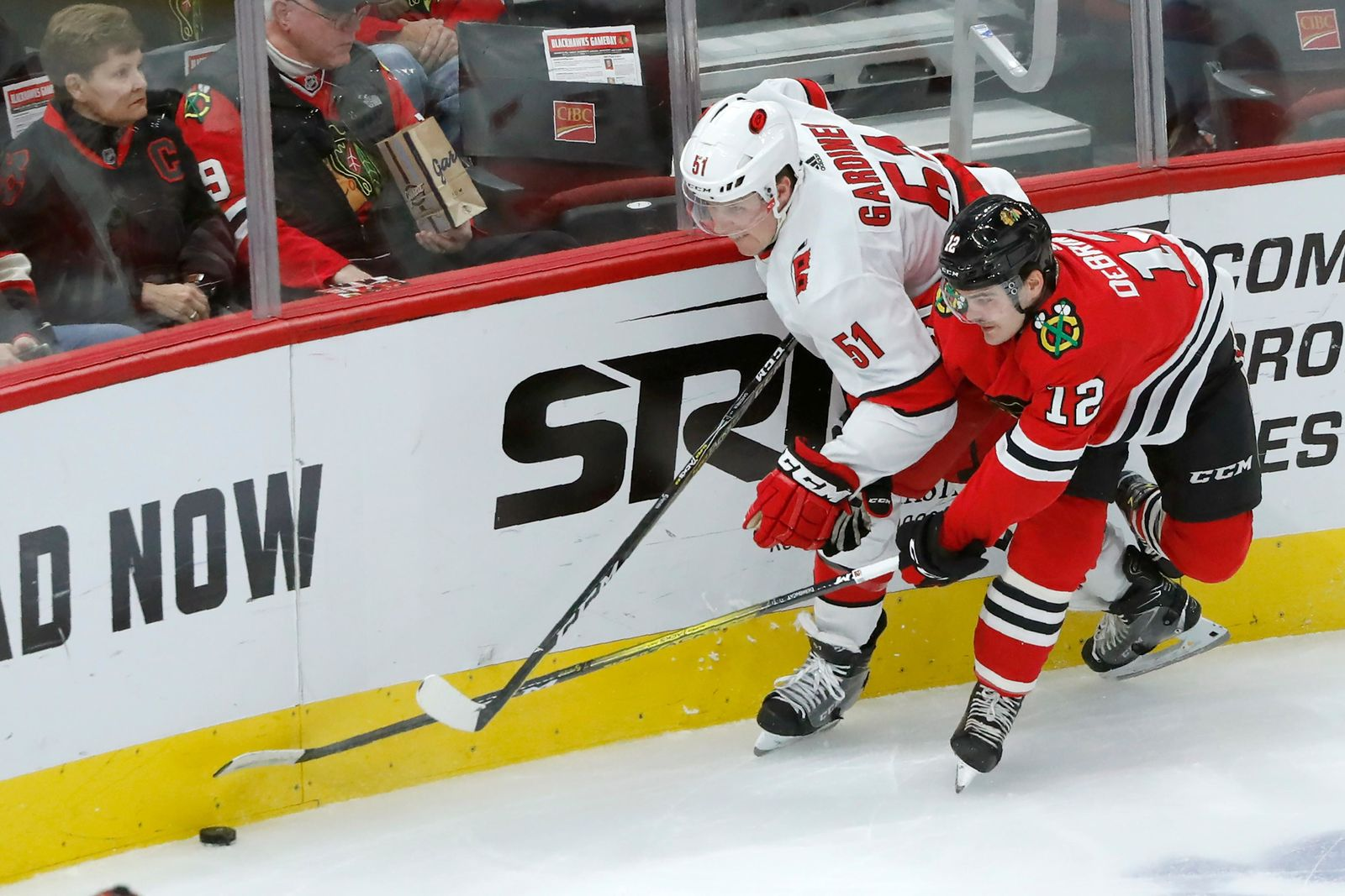Carolina Hurricanes' Jake Gardiner (51) and Chicago Blackhawks' Alex DeBrincat vie for the puck during the first period of an NHL hockey game Tuesday, Nov. 19, 2019, in Chicago. (AP Photo/Charles Rex Arbogast)