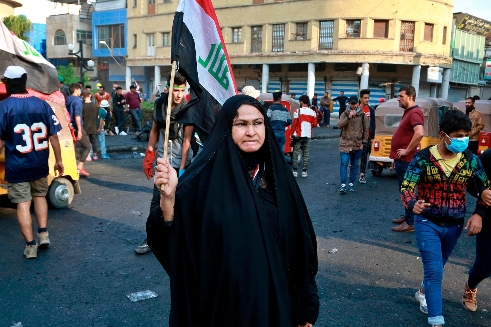 An Iraqi woman holds a national flag while anti-government protesters gather on Rasheed Street during ongoing protests in Baghdad, Iraq, Thursday, Nov. 28, 2019. Scores of protesters have been shot dead in the last 24 hours, amid spiraling violence in Baghdad and southern Iraq, officials said. (AP Photo/Khalid Mohammed)