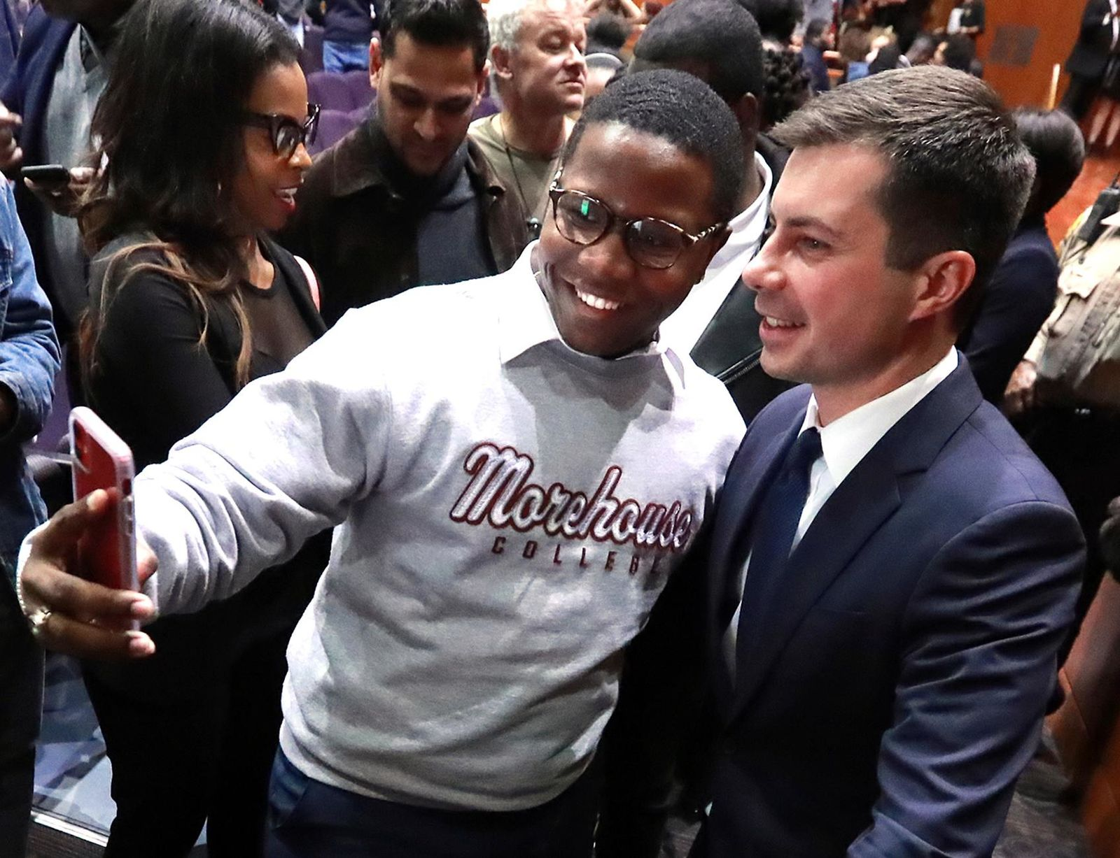 FILE- Morehouse College student Keron Campbell snaps a selfie with presidential hopeful Pete Buttigieg, Mayor of South Bend, Ind., at Morehouse College on Monday, Nov. 18, 2019, in Atlanta. (Curtis Compton/Atlanta Journal-Constitution via AP)