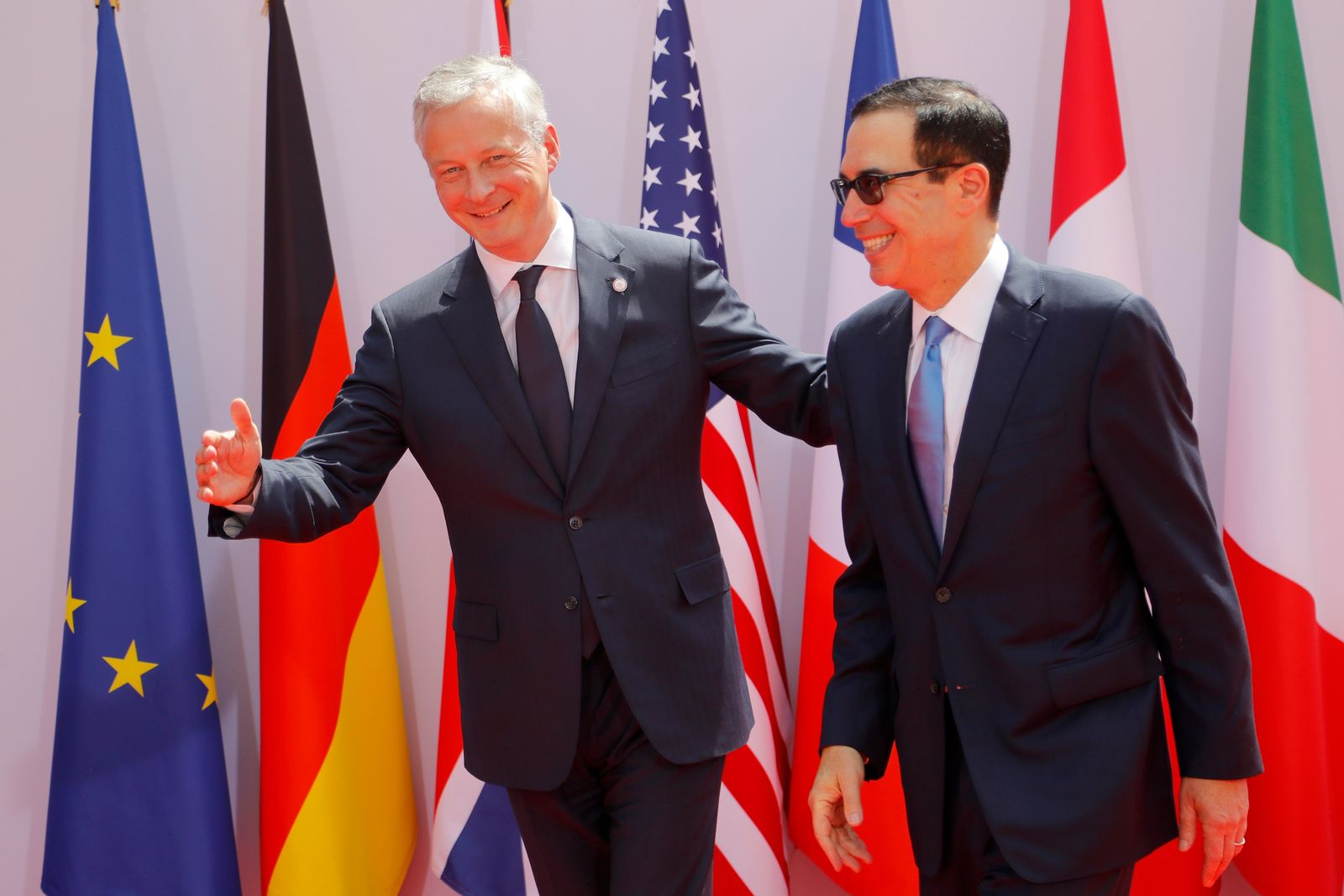 French Finance Minister Bruno Le Maire, left, welcomes Treasury Secretary Steve Mnuchin at the G-7 Finance Wednesday July 17, 2019 in Chantilly, north of Paris. (AP Photo/Michel Euler)