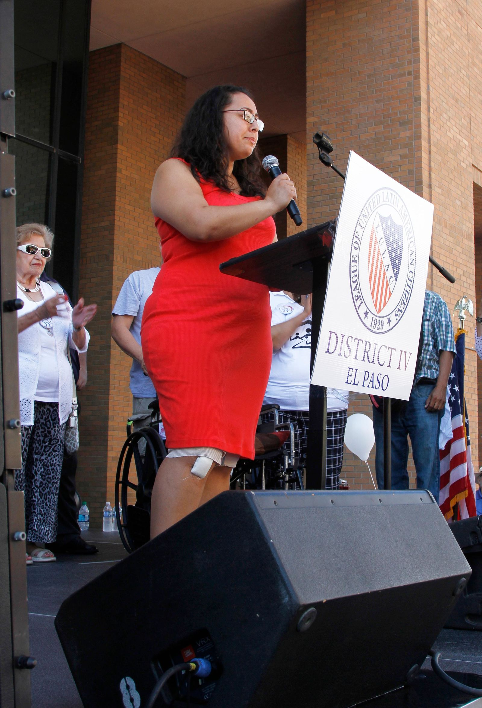 "Jessica Coca Garcia stands in front of her wheelchair addressing those gathered at the League of United Latin American Citizens' ""March for a United America"" Saturday, Aug. 10, 2019 in El Paso, Texas.   More than 100 people marched through the Texas border denouncing racism and calling for stronger gun laws one week after several people were killed in a mass shooting that authorities say was carried out by a man targeting Mexicans.  Garcia and her husband were injured during the mass shooting. (AP Photo/Cedar Attanasio)"