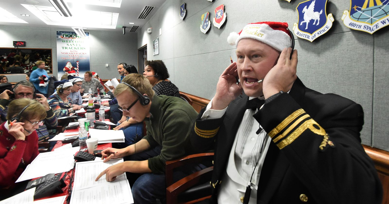 FILE – In this Dec. 24, 2017, file photo, Canadian Lt. Maj. Chris Hache takes a call while volunteering at the NORAD Tracks Santa center at Peterson Air Force Base in Colorado Springs, Colo. Hundreds of volunteers will help answer the phones again when the program resumes on Monday, Dec. 24, 2018, for the 63rd year. Children from around the world call to ask when Santa Claus will get to their house. (Jerilee Bennett/The Gazette via AP, File)