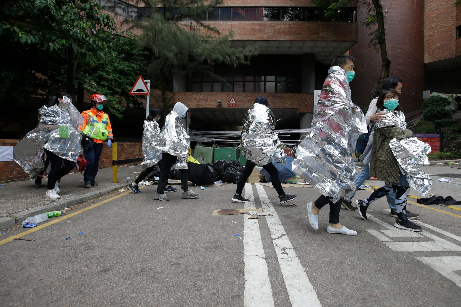 Injured protesters wrapped in blankets, walk through the campus of the Hong Kong Polytechnic University in Hong Kong, Tuesday, Nov. 19, 2019.{ } (AP Photo/Achmad Ibrahim)