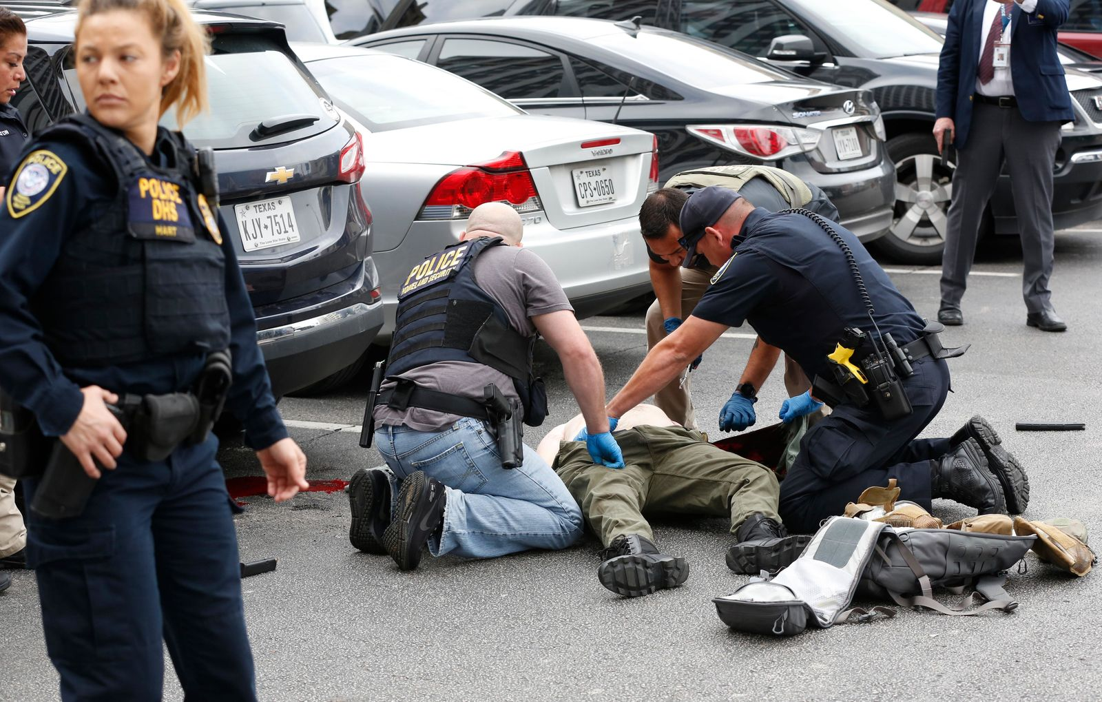 Law enforcement officers attend to an injured shooter in a parking lot after he fired shots at the Earle Cabell Federal Building in downtown Dallas, Monday, June 17, 2019. (Tom Fox/The Dallas Morning News) MANDATORY CREDIT, NO SALES, MAGS OUT,  TV OUT, INTERNET USE BY AP MEMBERS ONLY