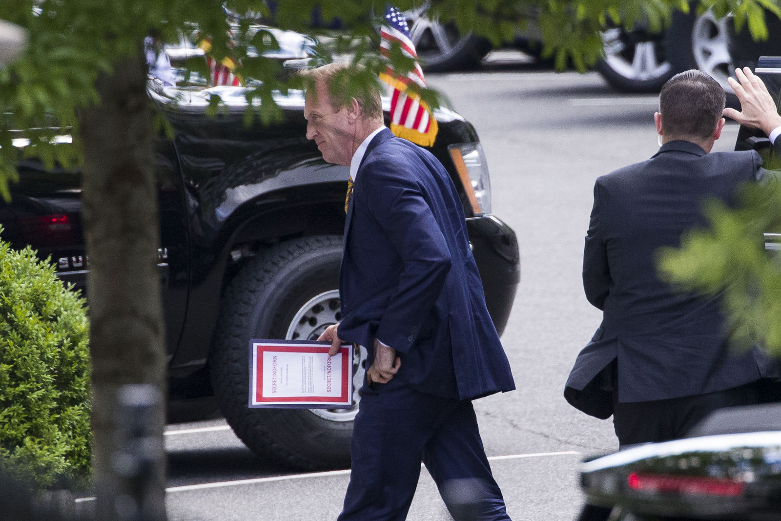 Outgoing acting Defense Secretary Patrick Shanahan arrives for a meeting with President Donald Trump about Iran carrying a folder marked secret, at the White House, Thursday, June 20, 2019, in Washington. (AP Photo/Alex Brandon)