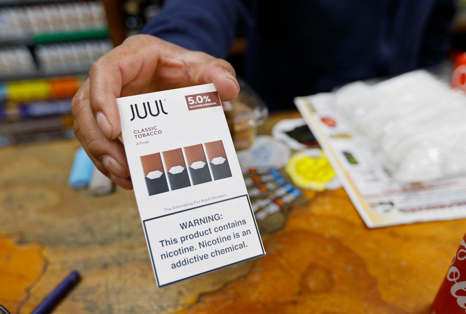 In this Monday, June 17, 2019, photo, a cashier displays a packet of tobacco-flavored Juul pods at a store in San Francisco. (AP Photo/Samantha Maldonado)