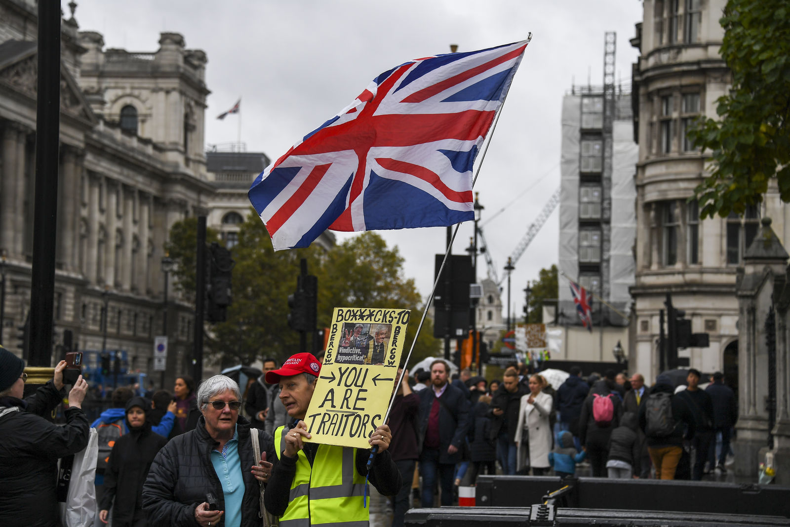 A pro Brexit demonstrator protests outside the Houses of Parliament, holding a placard and a Union flag, in London, Monday, Oct. 21, 2019. (AP Photo/Alberto Pezzali)