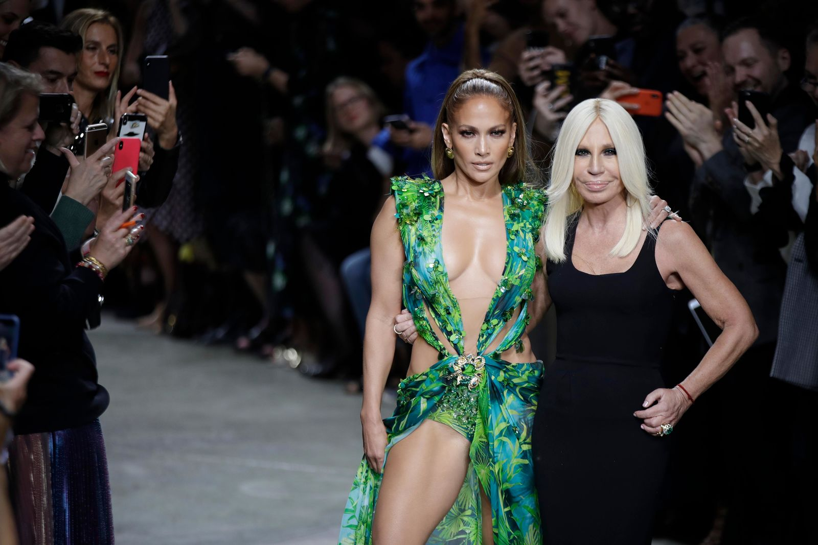 Actress Jennifer Lopez, left, and designer Donatella Versace accept applause at the conclusion of the Versace Spring-Summer 2020 collection, unveiled during the fashion week, in Milan, Italy, Friday, Sept. 20, 2019. (AP Photo/Luca Bruno)