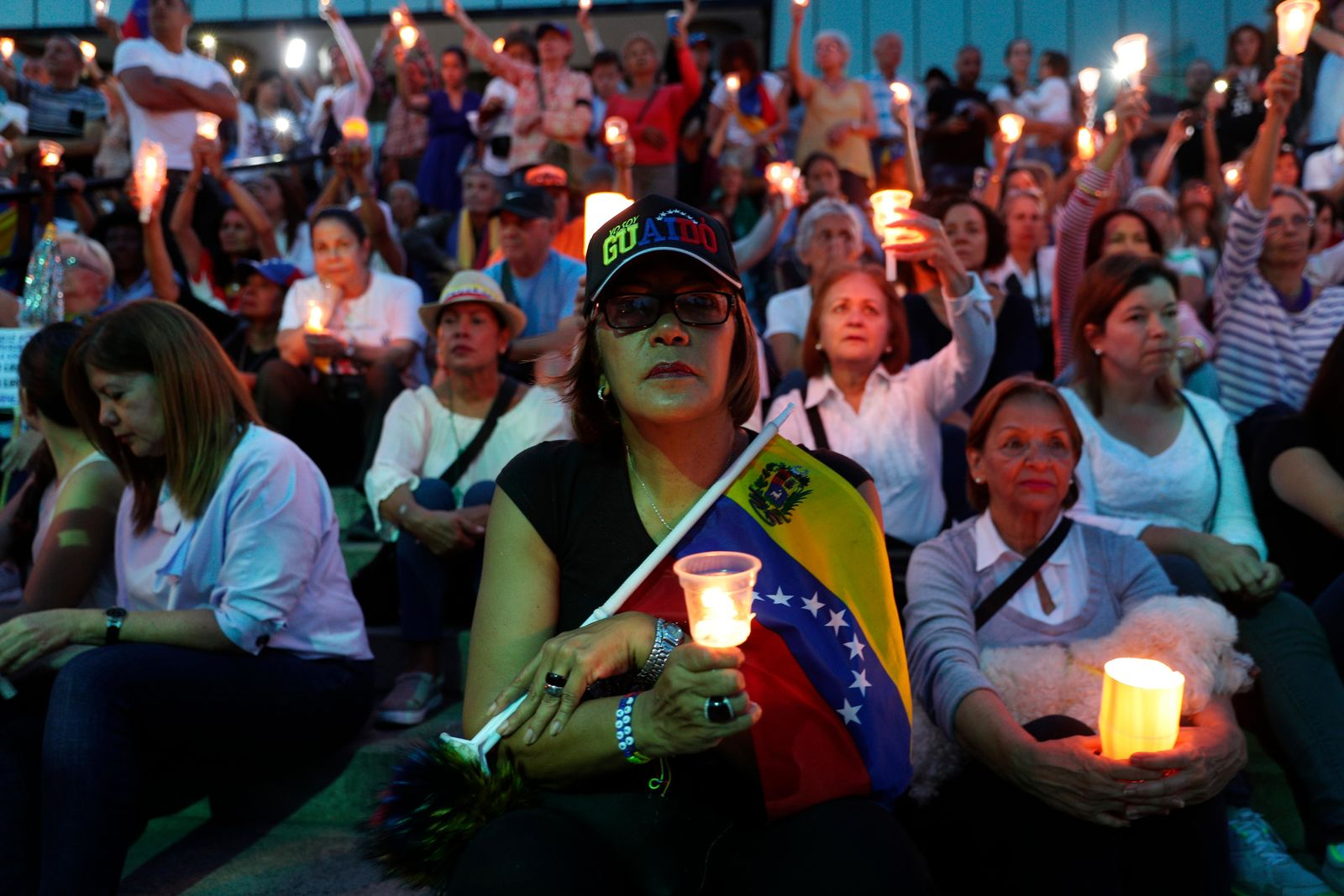 Opponents to Venezuela's President Nicolas Maduro hold a vigil for those killed in street fighting over the past week in Caracas, Venezuela, Sunday, May 5, 2019. Opposition leader Juan Guaidó called in vain for a military uprising to overthrow President Nicolas Maduro, and five people were killed in clashes between protesters and police. (AP Photo/Martin Mejia)