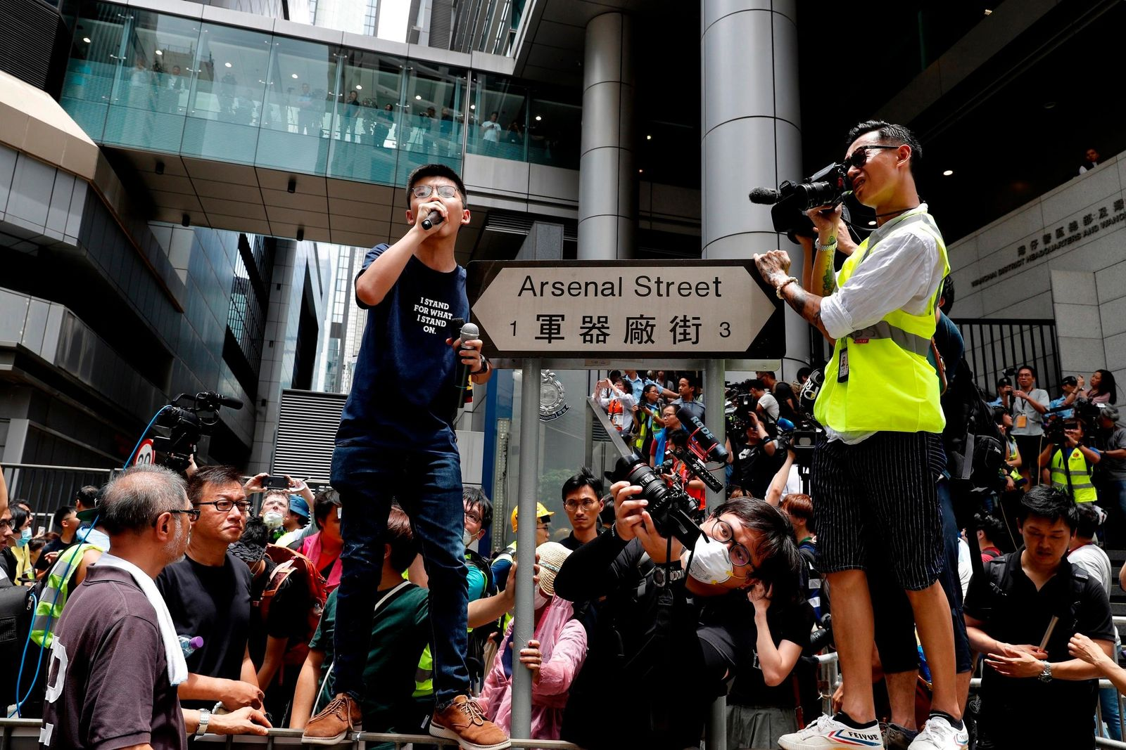 FILE - In this June 21, 2019, file photo, pro-democracy activist Joshua Wong, center left, speaks as protesters surround the police headquarters in Hong Kong. (AP Photo/Vincent Yu, File)