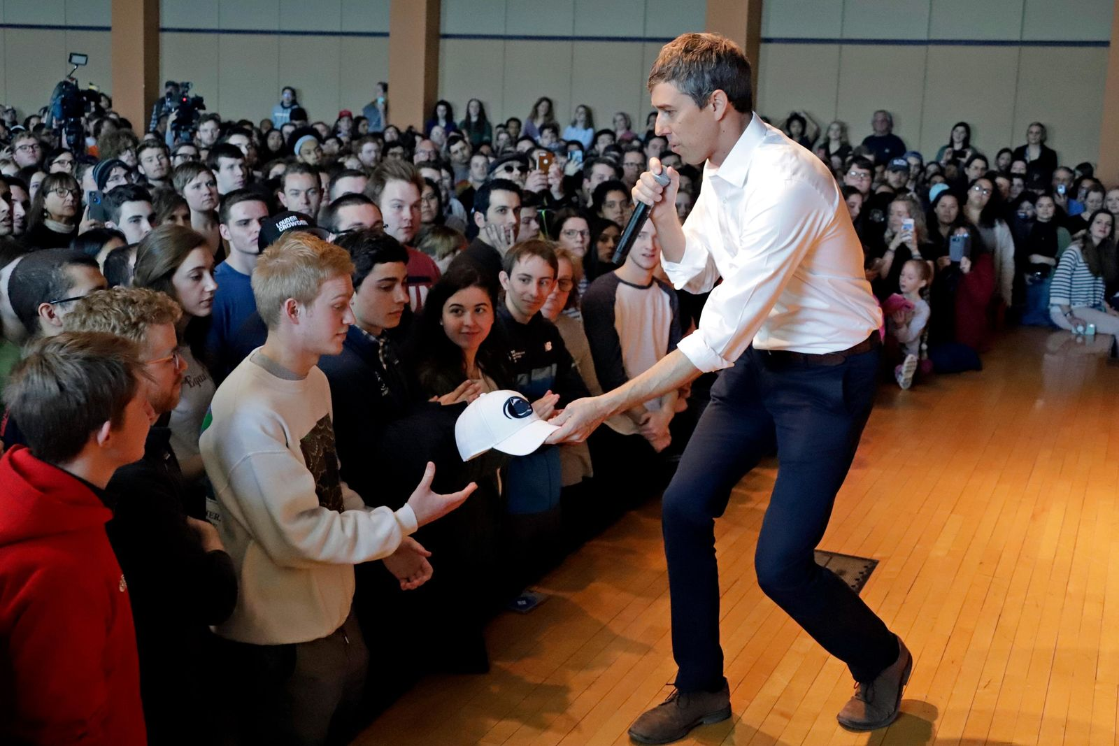 Democratic presidential candidate Beto O'Rourke, right, hands his cap to Tom Sowers, a freshman at Penn State from State College, Pa., as he speaks at an event at The Hub Robison Center on the Penn State campus in State College, Pa., Tuesday, March 19, 2019. (AP Photo/Gene J. Puskar)