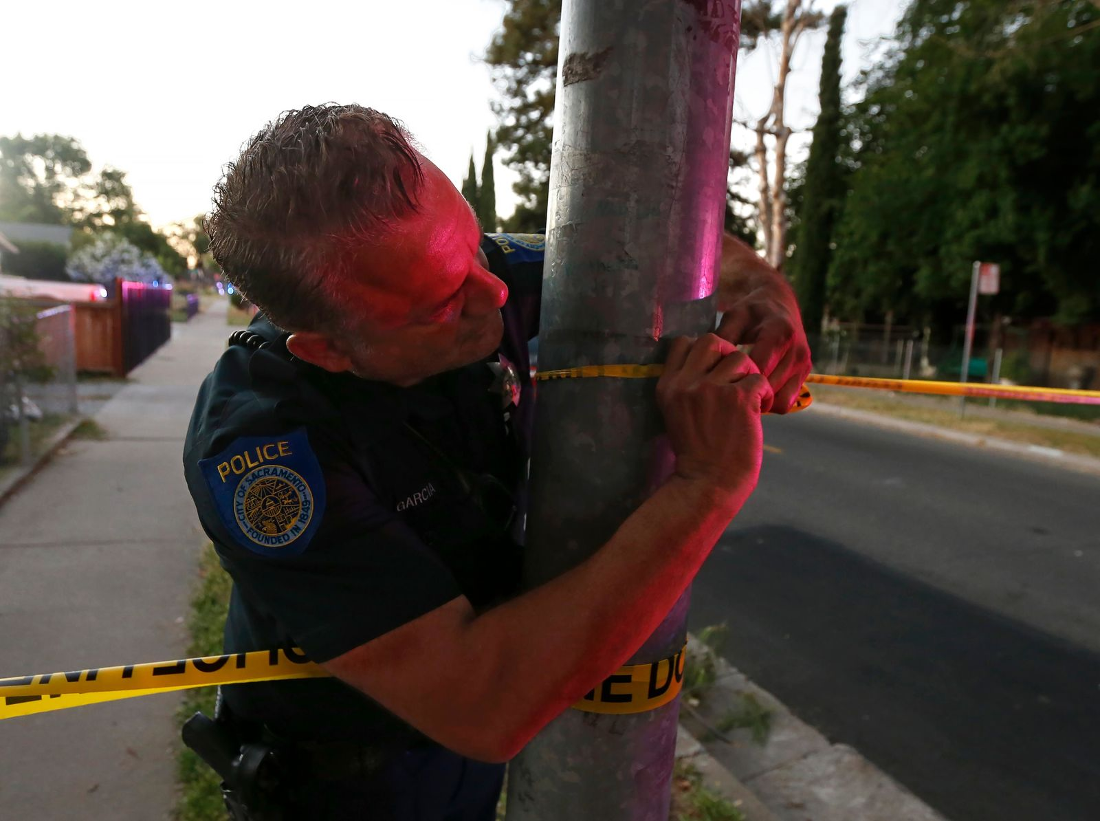 A Sacramento Police officer puts up crime scene tape near a home that authorities have surrounded where a gunman has taken refuge after shooting a Sacramento police officer, Wednesday, June 19, 2019, in Sacramento, Calif. (AP Photo/Rich Pedroncelli)