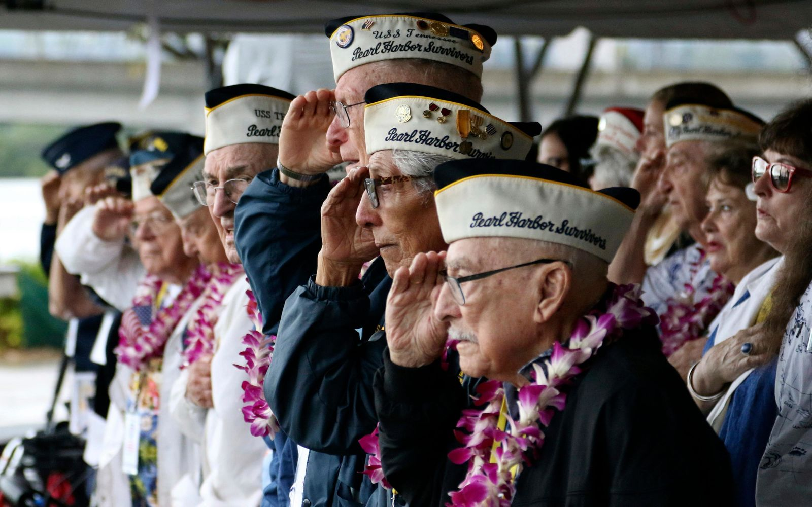 FILE - In this Dec. 7, 2018, file photo, Pearl Harbor survivors salute during the National Anthem at a ceremony in Pearl Harbor, Hawaii marking the 77th anniversary of the Japanese attack. Survivors and members of the public are expected to gather in Pearl Harbor on Saturday, Dec. 7, 2019, to remember those killed when Japanese planes bombed the Hawaii naval base 78 years ago and launched the U.S. into World War II. Organizers plan for about a dozen survivors of the attack to attend the annual ceremony, the youngest of whom are now in their late 90s. (AP Photo/Audrey McAvoy, File)