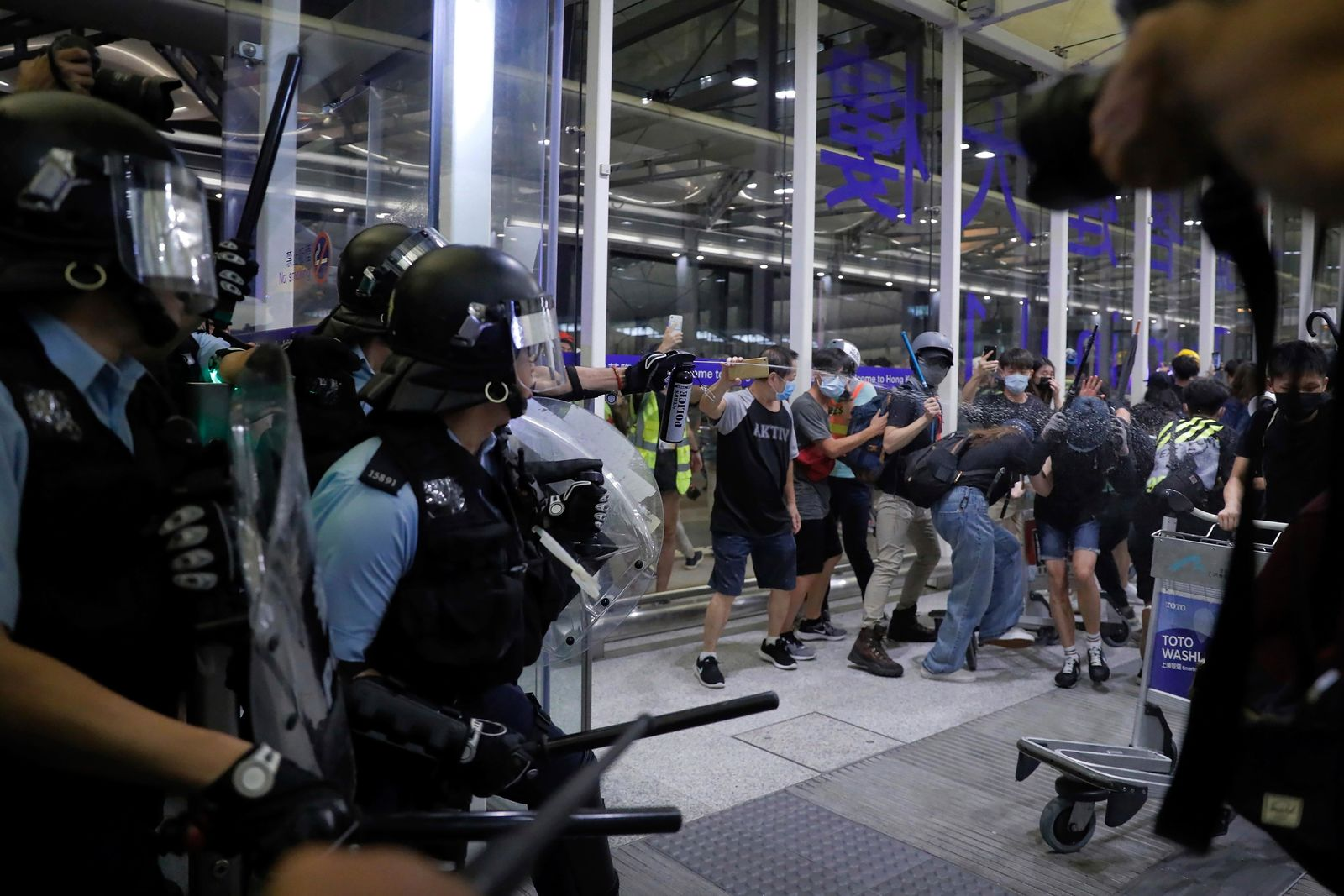 Policemen in riot gears use pepper spray on the protesters during a demonstration at the Airport in Hong Kong, Tuesday, Aug. 13, 2019. Chaos has broken out at Hong Kong's airport as riot police moved into the terminal to confront protesters who shut down operations at the busy transport hub for two straight days. (AP Photo/Kin Cheung)