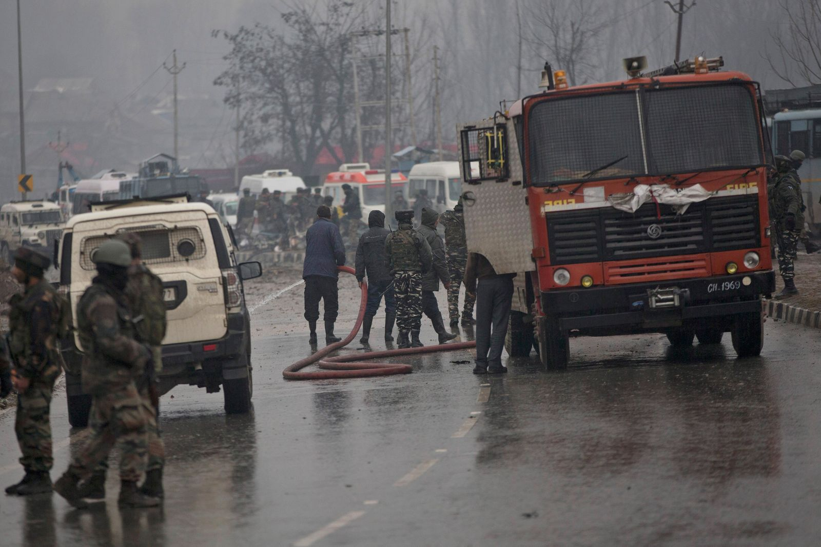 Indian firemen spray water on a road to wash away blood after an explosion in Pampore, Indian-controlled Kashmir, Thursday, Feb. 14, 2019. (AP Photo/Dar Yasin)