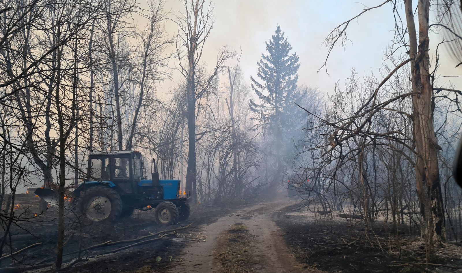 Chernobyl zone workers extinguish a forest fire burning near the village of Volodymyrivka, in the exclusion zone around the Chernobyl nuclear power plant, Ukraine, Sunday April 5, 2020. (AP Photo/Yaroslav Yemelianenko)