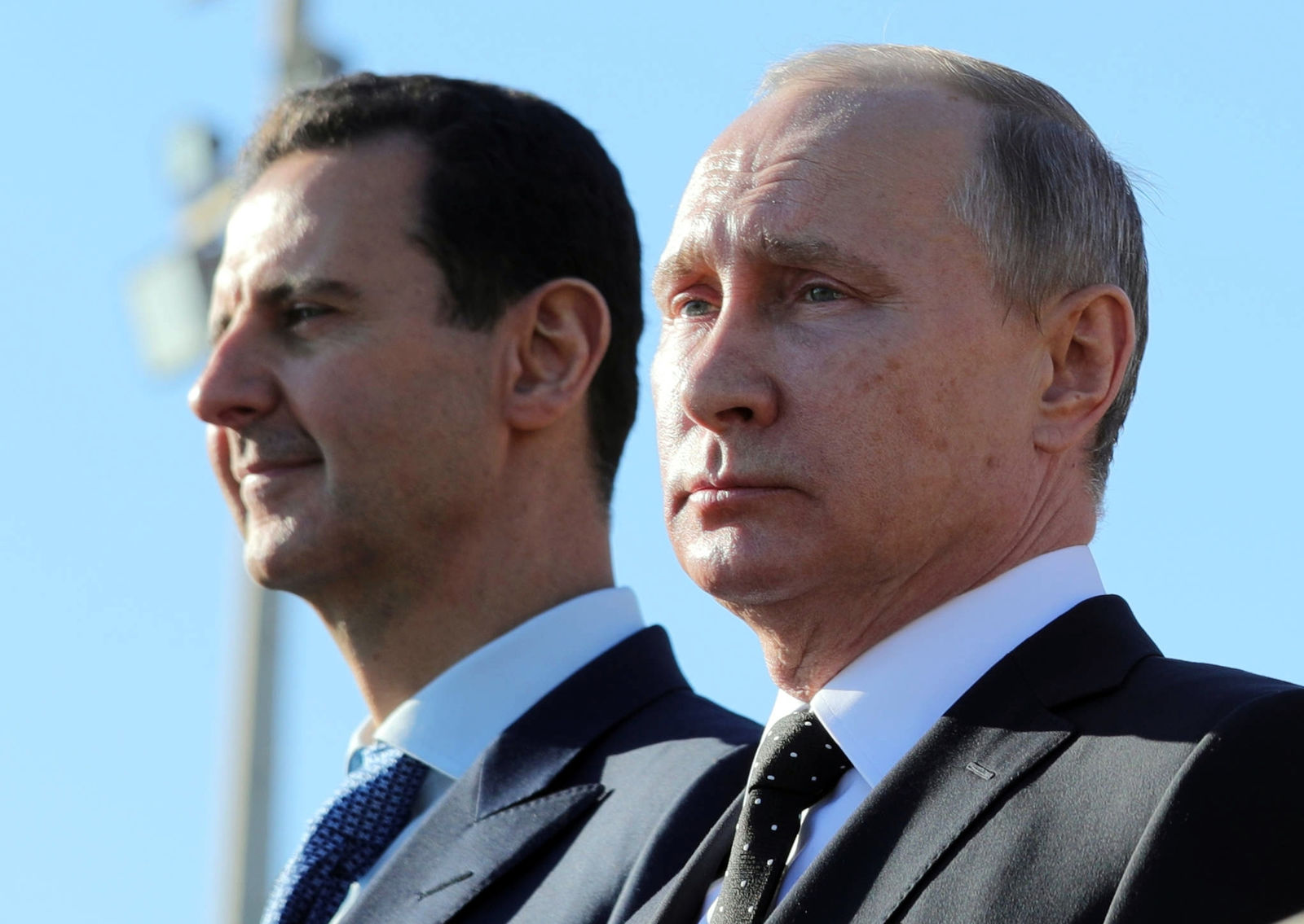 FILE - This Dec. 11, 2017 file photo, shows Russian President Vladimir Putin, right, and Syrian President Bashar Assad watching troops march at the Hemeimeem air base in Syria. Russia and Iran have been strong backers of Assad, helping him in his bid to regain control of territories. (Mikhail Klimentyev, Sputnik, Kremlin Pool Photo via AP, File)