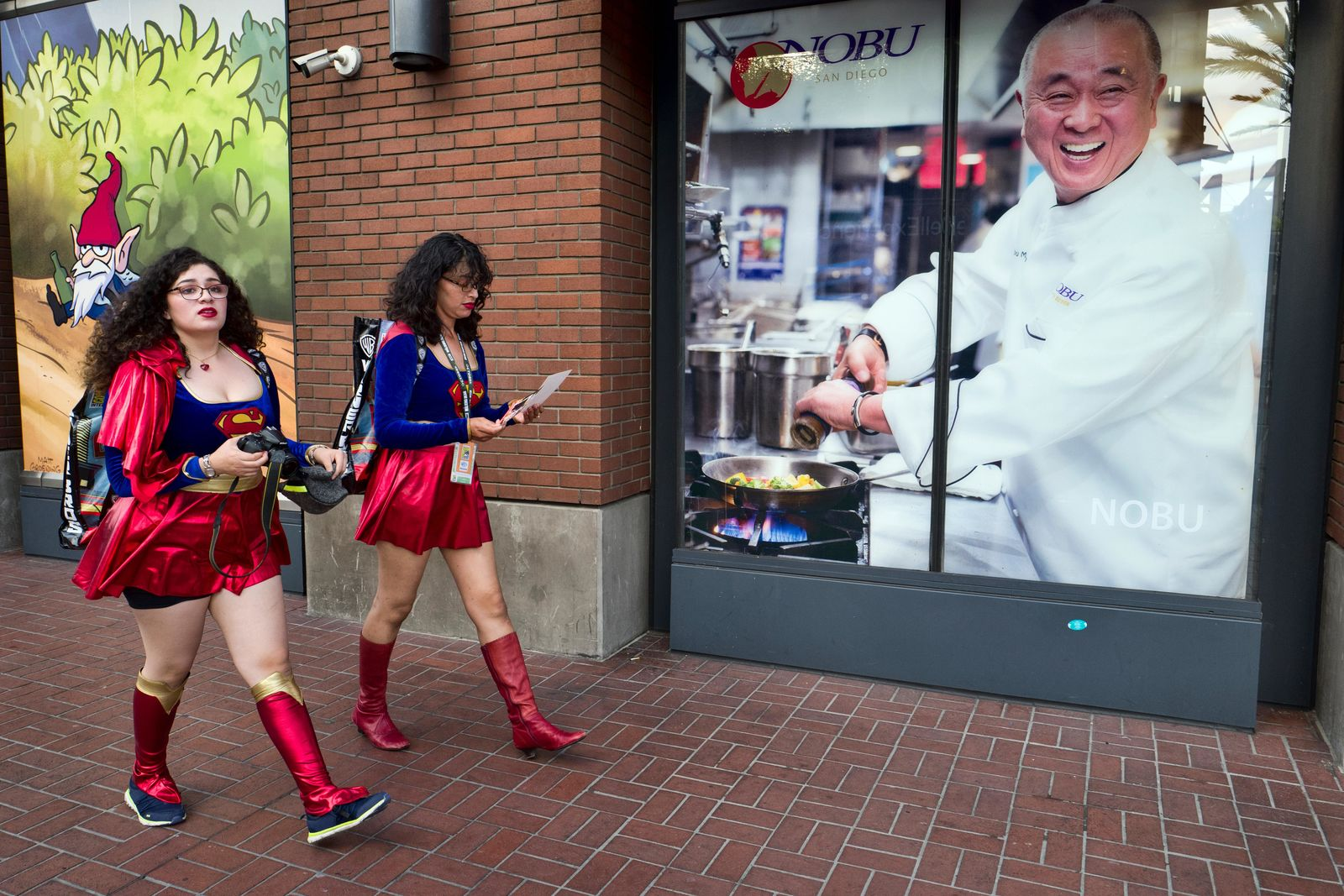 Women dressed as Supergirl walk along a downtown San Diego street on Preview Night of the 2018 Comic-Con International Wednesday, July 18, 2018, in San Diego. (AP Photo/Richard Vogel)